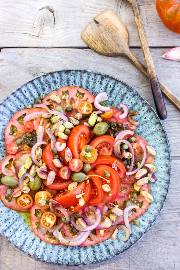 Erfrischender Tomatensalat mit Pistazien und Kapern + extra Rezept für ein knusprig leckeres Focaccia. Perfekt für das nächste Grillfest!