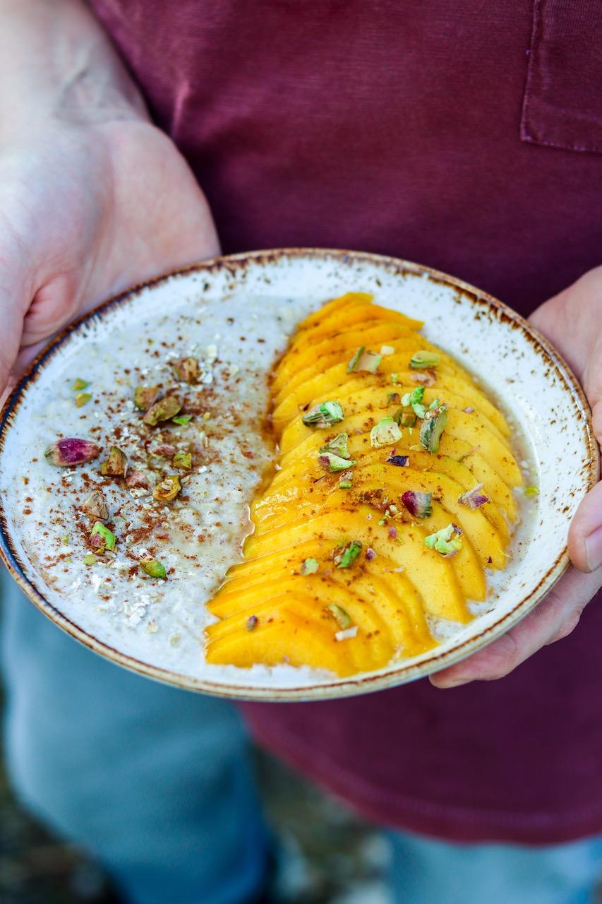 Leckeres Porridge aus Mandelmilch mit frischer Mango, Kardamom, Zimt und Pistazien