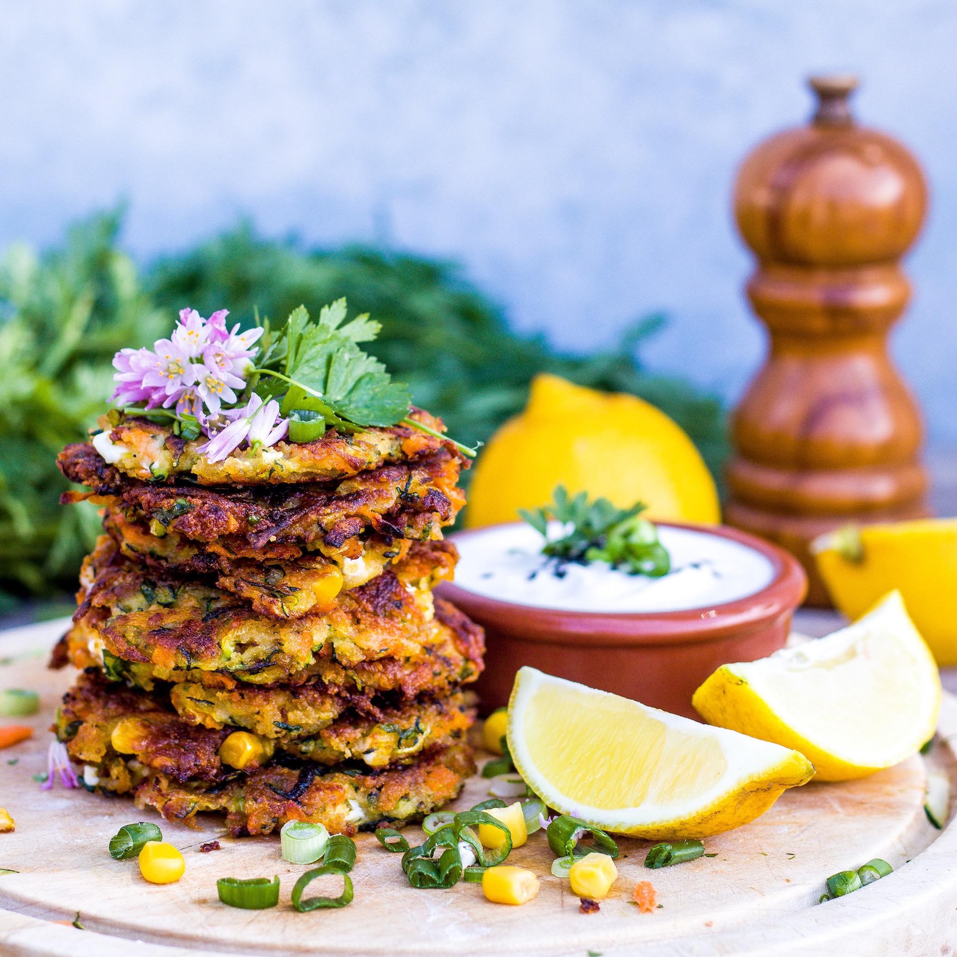 Schnelle und einfache Reibekuchen aus Zucchini, Karotten, Mais und Feta. Super lecker mit etwas Zitrone und Tsatziki. #fritter #vegetarisch #zucchini #gemüsepuffer #reibekuchen