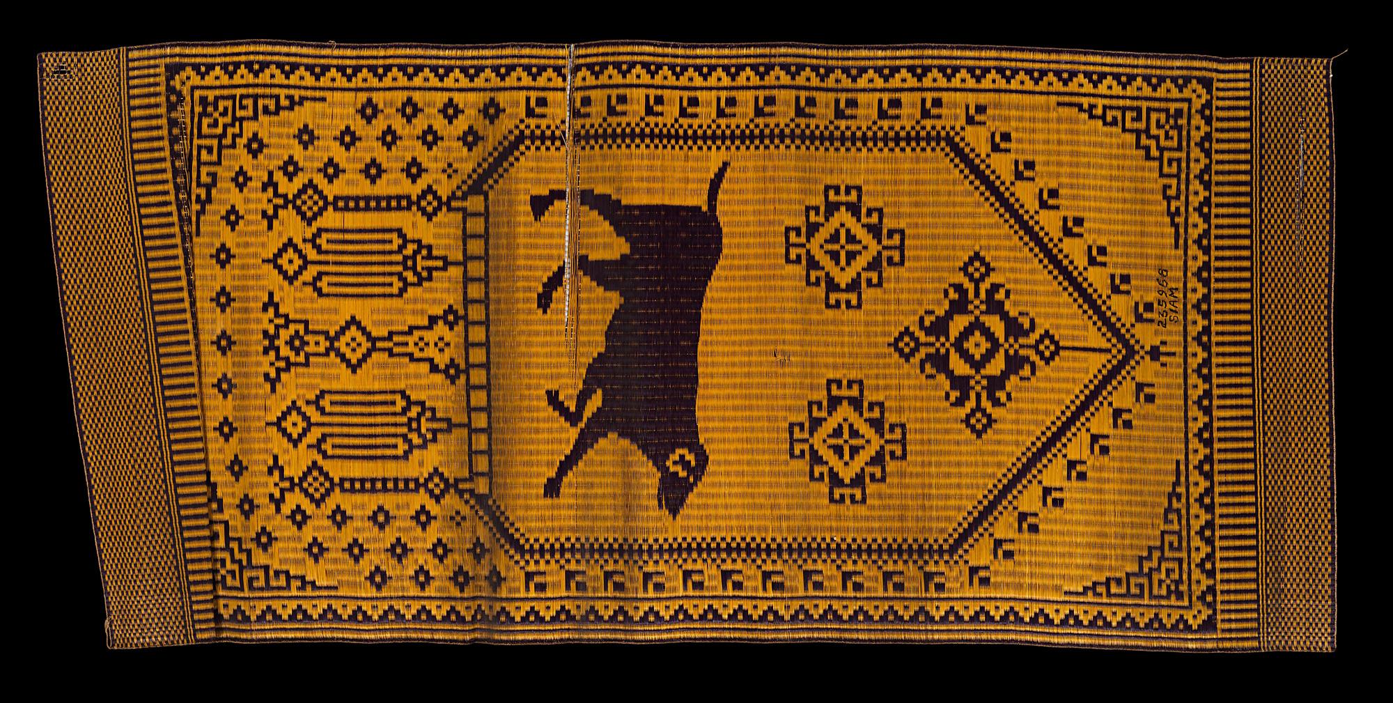 """Chantaboon"" Woven Reed Mat with Astrological Sign of the Dog Chanthaburi Province Gift from King Chulalongkorn to the Smithsonian Institution, 1904 188 x 86 cm Courtesy of the Smithsonian Institution, Department of Anthropology; E235968; Photo by Jim Di Loreto   เสื่อ ""จันทบูร"" ทอรูปสุนัข สัญลักษณ์นักษัตรปีจอ จังหวัดจันทบุรี ของขวัญพระราชทานจากพระบาทสมเด็จพระจุลจอมเกล้าเจ้าอยู่หัว แก่สถาบันสมิธโซเนียน พ.ศ. ๒๔๔๗ ๑๘๘ x ๘๖ ซม. ได้รับความอนุเคราะห์จากฝ่ายมานุษยวิทยา สถาบันสมิธโซเนียน ; E235968; ถ่ายโดยจิม ดิลอเรโต"