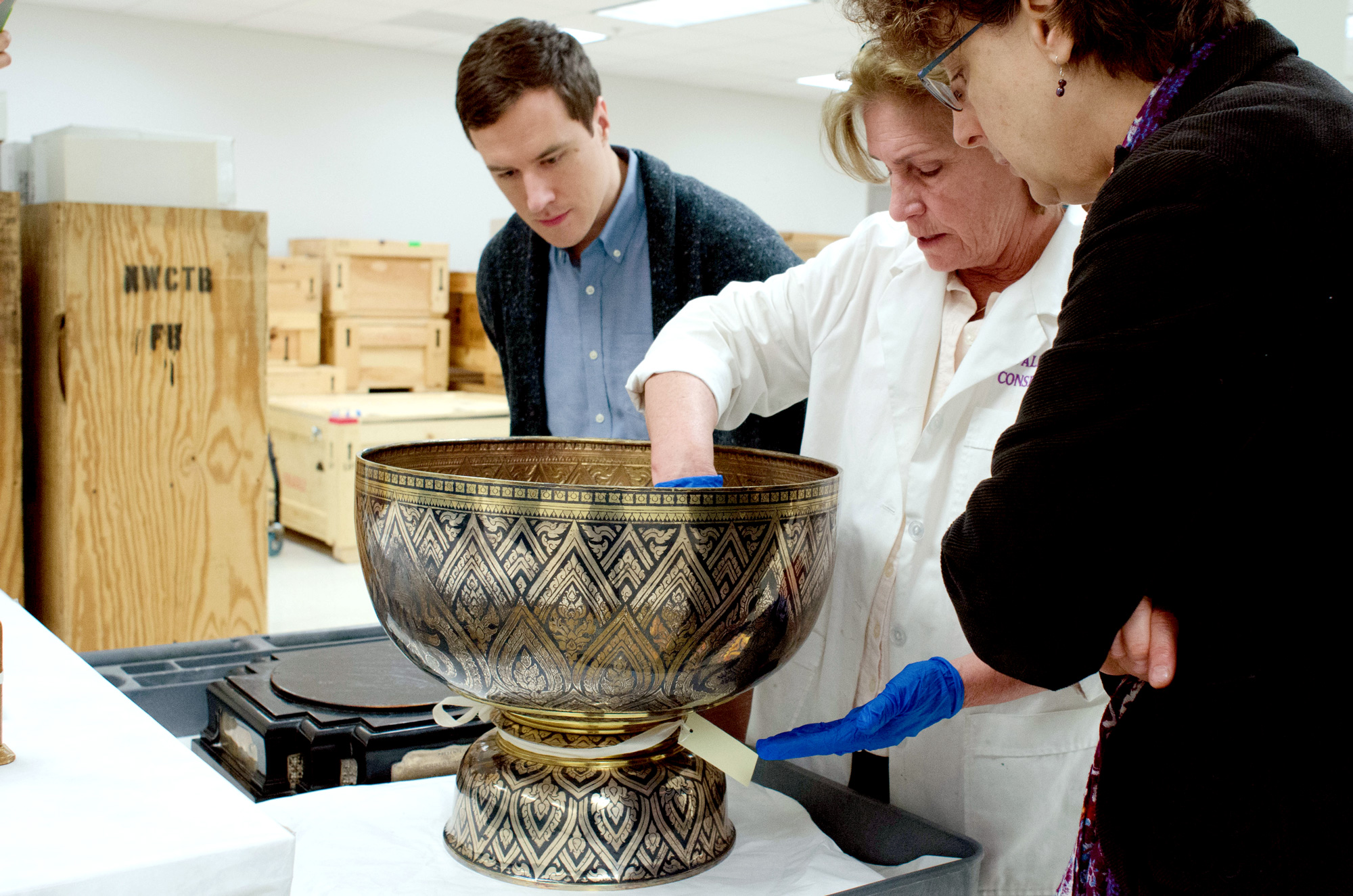 12/11/17 - National Archives Building, Washington, DC: Curator Trevor Merrion and Kim Koons of the National Archives (right) watch as conservator Cathy Valentour explains the necessary conservation treatment for the gilded niello bowl that was gifted to President Herbert Hoover by King Prajadhipok during his U.S. visit in 1931.
