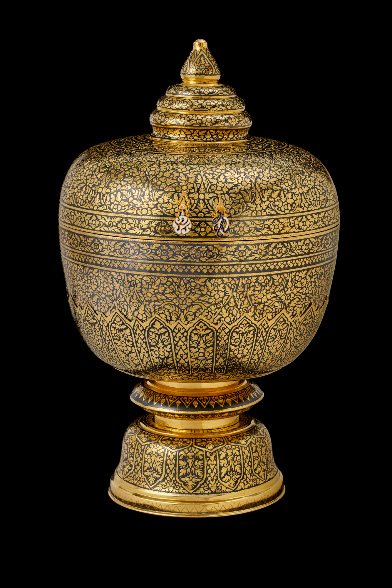 Gold Niello Covered Bowl with Gold Royal Cyphers Gift from King Bhumibol Adulyadej to President George W. Bush, 2003 33.7 x 20.5 cm Courtesy of the George W. Bush Presidential Library and Museum; FO.333417.2.a-b  โถถมทองประดับอักษรพระปรมาภิไธยพระบาทสมเด็จพระปรมินทรมหาภูมิพลอดุลยเดช บรมนาถบพิตร ภายใต้พระมหาพิชัยมงกุฎ และอักษรพระนามาภิไธยสมเด็จพระนางเจ้าสิริกิติ์ พระบรมราชินีนาถ ภายใต้พระมหามงกุฎ ของขวัญพระราชทานจากพระบาทสมเด็จพระปรมินทรมหาภูมิพลอดุลยเดช แก่ประธานาธิบดีจอร์จ ดับเบิลยู. บุช พ.ศ. ๒๕๔๖ ๓๓.๗ x ๒๐.๕ ซม. ได้รับความอนุเคราะห์จากพิพิธภัณฑ์และหอสมุดประธานาธิบดีจอร์จ ดับเบิลยู. บุช; FO.333417.2.a-b