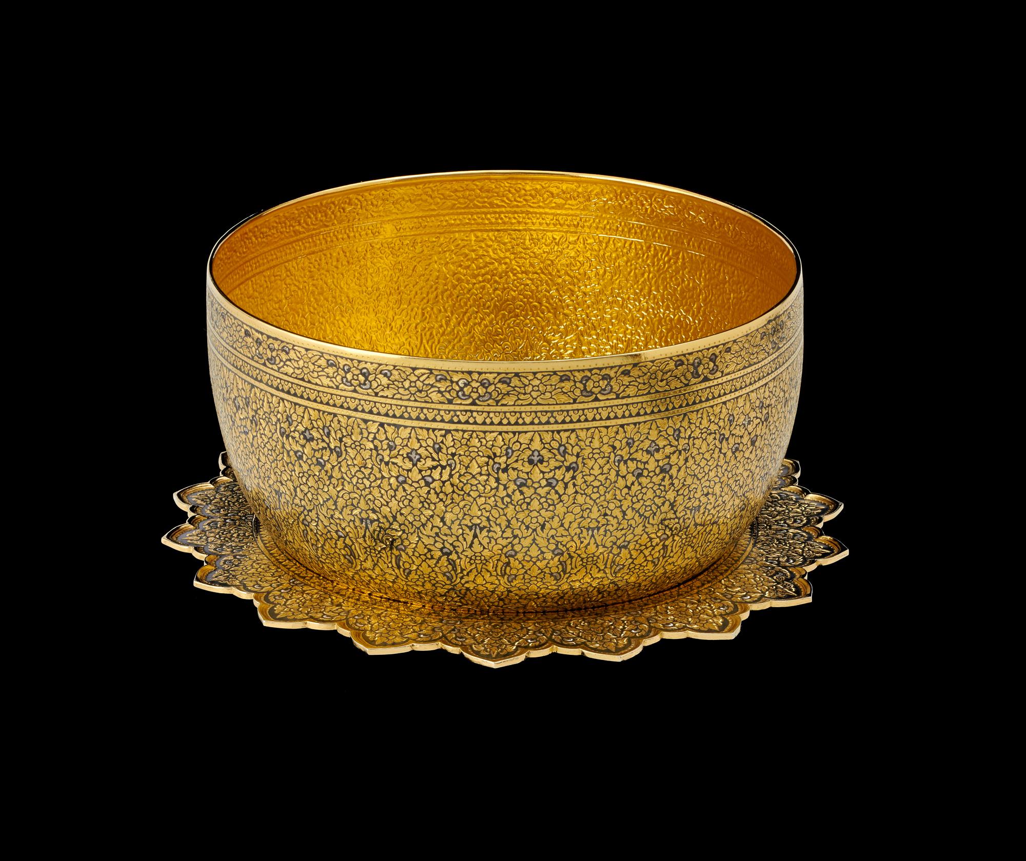 Gold Niello Bowl and Tray Gift from Queen Sirikit to President George H.W. Bush and First Lady Barbara Bush, 1991 18 x 11.5 cm Courtesy of the George Bush Presidential Library and Museum; 91.70108.6  ขันน้ำพร้อมพานถมทอง ลายพุดตานใบเทศ ของขวัญพระราชทานจากสมเด็จพระนางเจ้าสิริกิติ์ พระบรมราชินีนาถ แก่ประธานาธิบดีจอร์จ เอช. ดับเบิลยู. บุช และนางบาร์บารา บุช สุภาพสตรีหมายเลขหนึ่ง พ.ศ. ๒๕๓๔ ๑๘ x ๑๑.๕ ซม. ได้รับความอนุเคราะห์จากพิพิธภัณฑ์และหอสมุดประธานาธิบดีจอร์จ บุช; 91.70108.6
