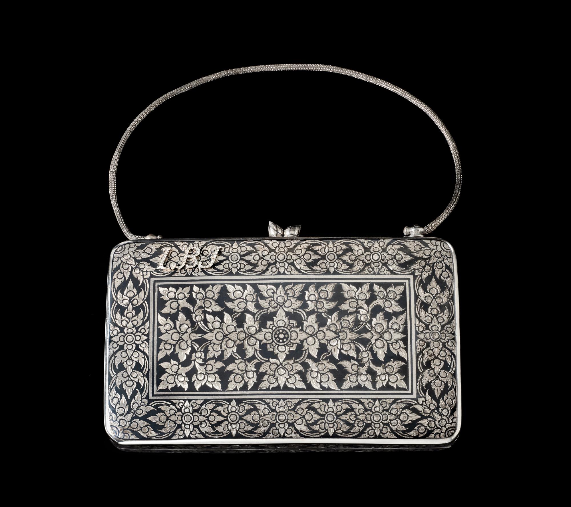 "Silver Niello Purse Embellished with Diamonds Gift from Queen Sirikit to First Lady Claudia ""Lady Bird"" Johnson, 1966 12.1 x 17.7 x 3.6 cm Courtesy of the Lyndon B. Johnson Presidential Library and Museum; 1966.51.6  กระเป๋าถมเงินประดับเพชร ของขวัญพระราชทานจากสมเด็จพระนางเจ้าสิริกิติ์ พระบรมราชินีนาถ แก่นางคลอเดีย ""เลดี้ เบิร์ด"" จอห์นสัน สุภาพสตรีหมายเลขหนึ่ง พ.ศ. ๒๕๐๙ ๑๒.๑ x ๑๗.๗ x ๓.๖ ซม. ได้รับความอนุเคราะห์จากพิพิธภัณฑ์และหอสมุดประธานาธิบดีลินดอน บี. จอห์นสัน; 1966.51.6"