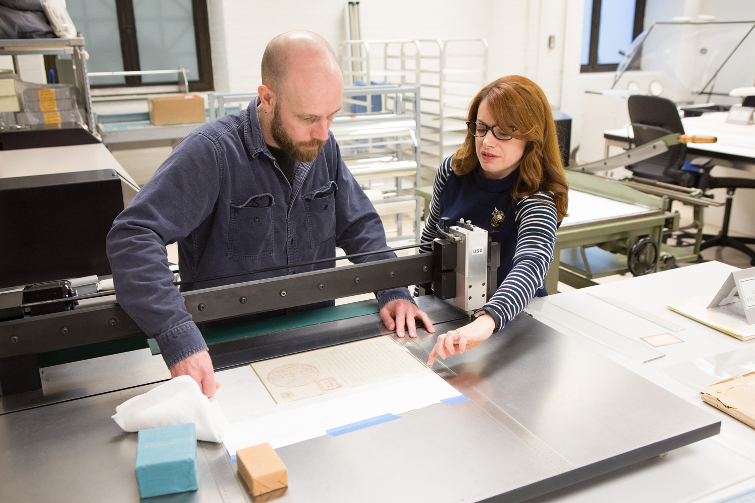 "Working in the National Archives Conservation Lab, Exhibits Technician Vincent Carney (left) and Exhibits Conservator Abigail Aldrich (right) encapsulate the 1861 ""Elephant letter"" from King Mongkut to President Buchanan, 2018 Washington, D.C. NARA photograph by Jeff Reed"