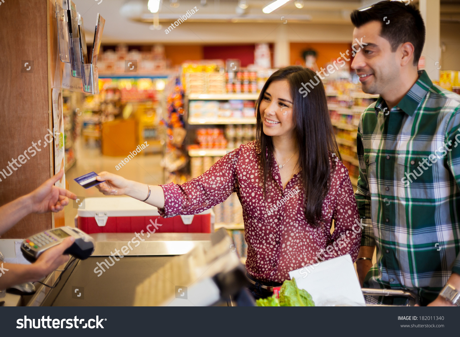 stock-photo-beautiful-young-brunette-and-her-boyfriend-buying-some-groceries-at-the-supermarket-and-paying-with-182011340.jpg