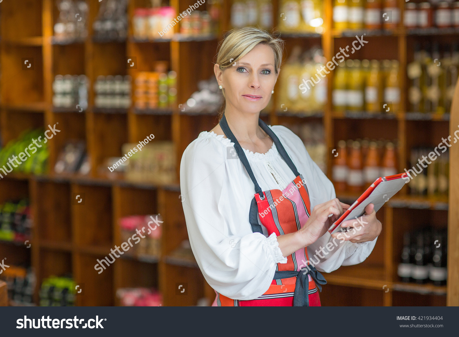 stock-photo-woman-holding-digital-tablet-in-grocery-store-421934404.jpg
