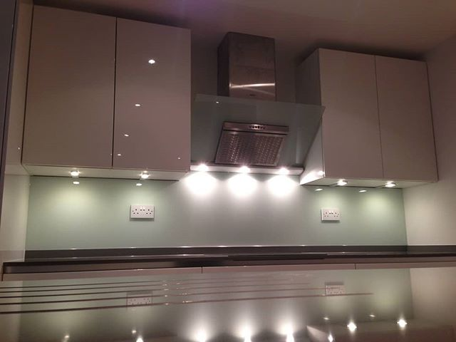 Glass kitchen splashback with under cupboard lighting used to great effect