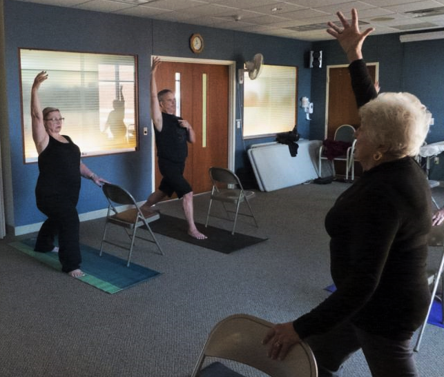 """Yoga instructor Paul Mross, who taught yoga for the new study, leads a different class in Dodgeville. """"When it comes to fall prevention, we want to help you stand strong, but it's not just standing,"""" he says. """"We move in our life, we are reaching, doing whatever it is we need to function, and yoga helps us remain stable then, too."""" DAVID TENENBAUM, UNIVERSITY COMMUNICATIONS"""