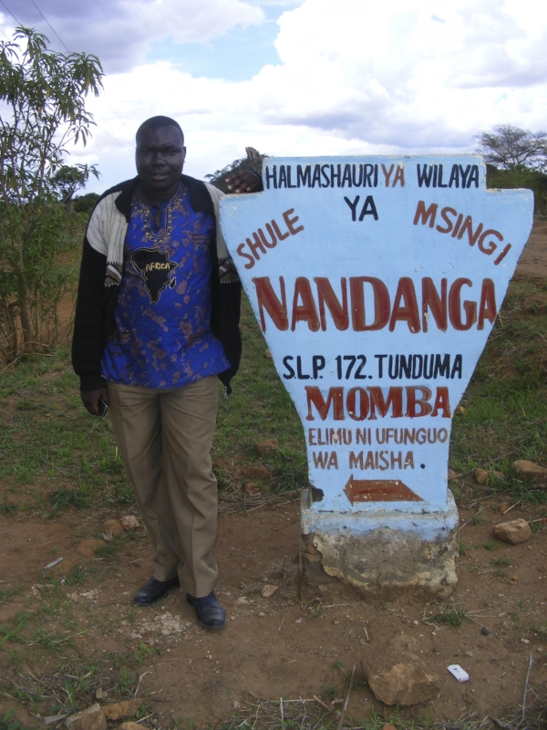 Keneth Simbaya, the founder of Pure Water Joy, standing at the entrance to Nandanga, a rural village in the Mbeya region of Tanzania