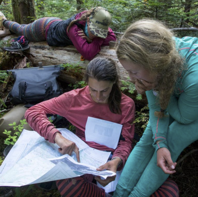 The group assess their options after reaching an impassible tributary that is blocking them from reaching a logging road, their lifeline out. Photo: Maranda Stopol.