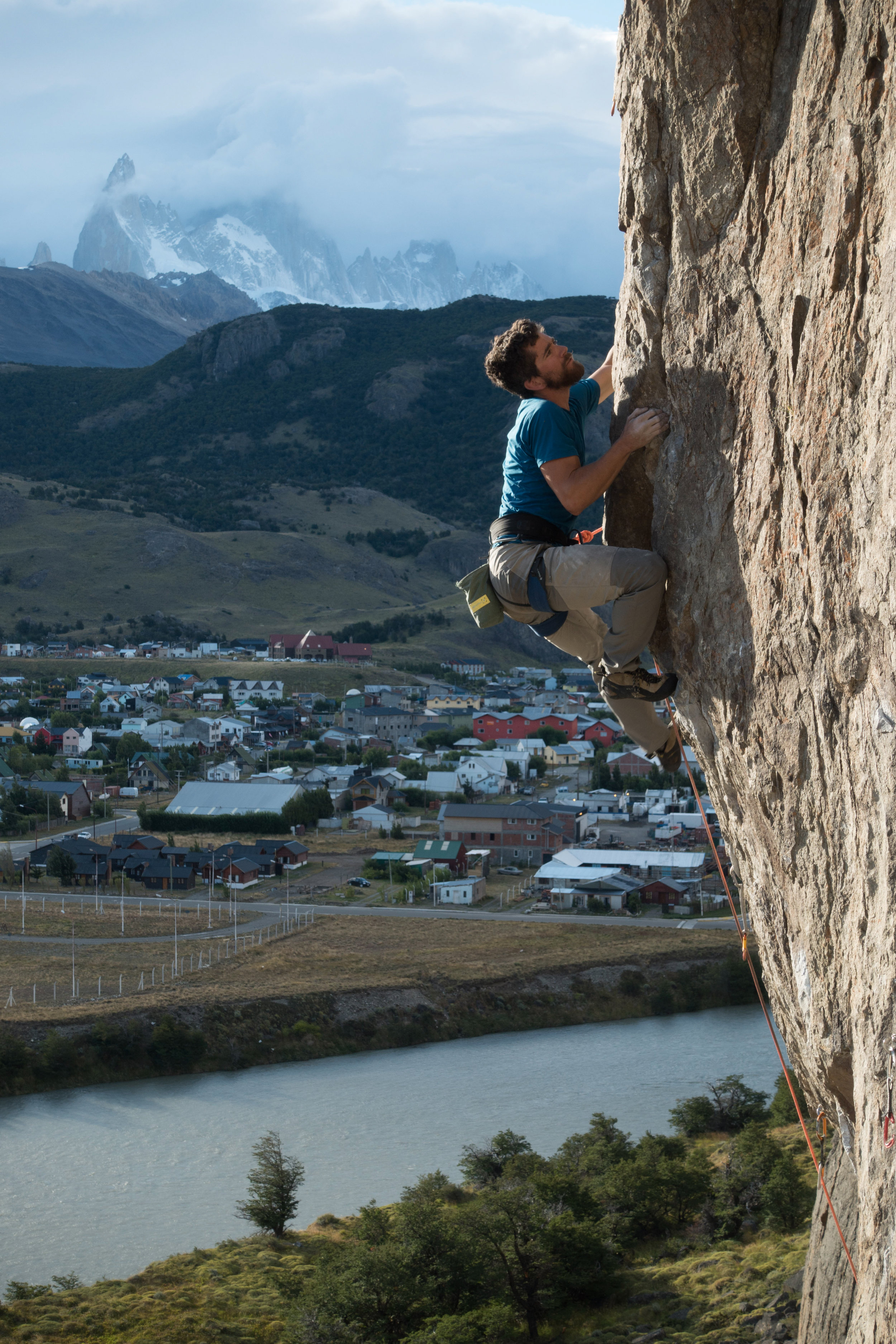 Sam Lambert sport climbing in the sun while a storm rages in the mountains. Photo by Michelle Kadatz.