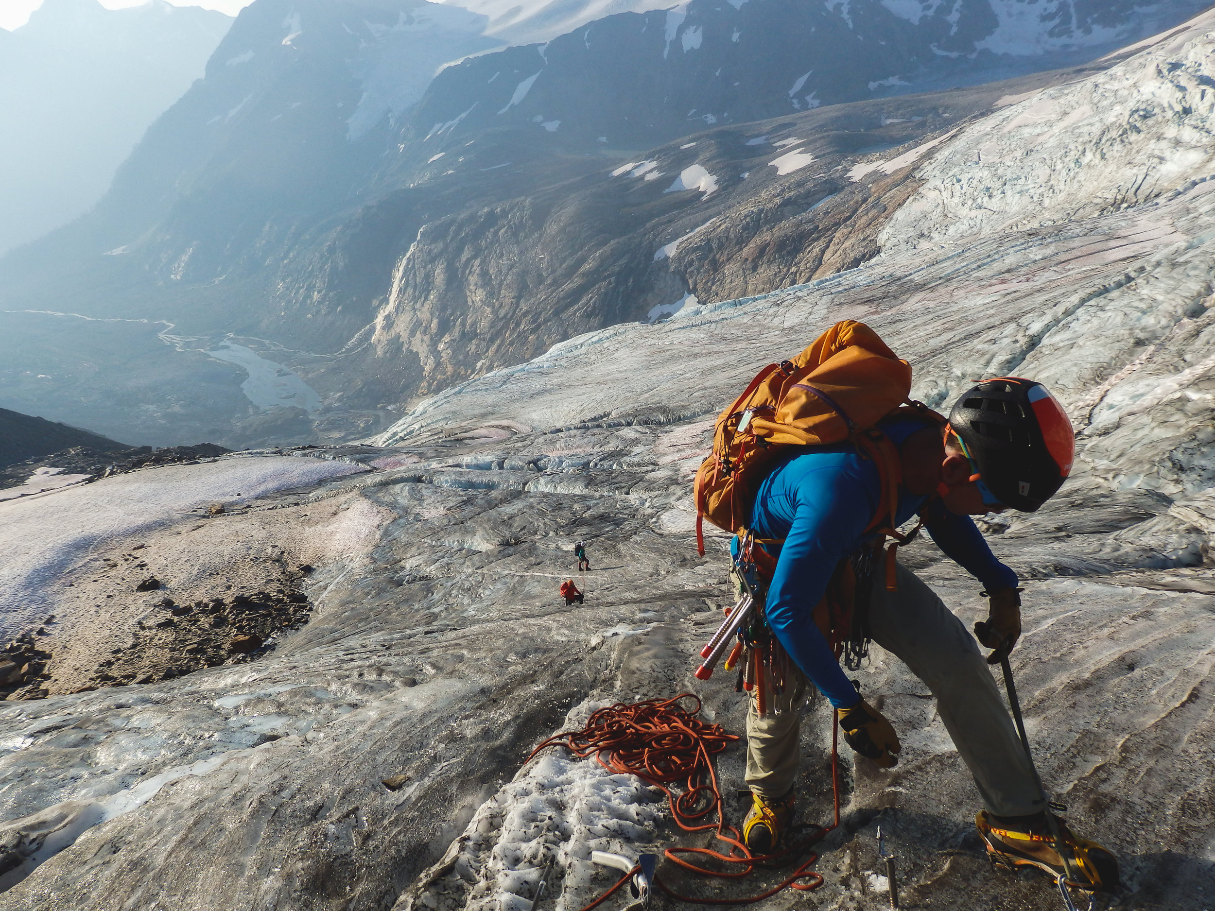 """Larry Shiu placing protection during the climb of """"The Riddle"""" glacier, en route to False Hallam (a.k.a. """"Helium"""") Peak. Behind him are Serena Polt and Wendell Martin. Camp is seen down the valley in the distance. Photo: Gadi Maayan."""