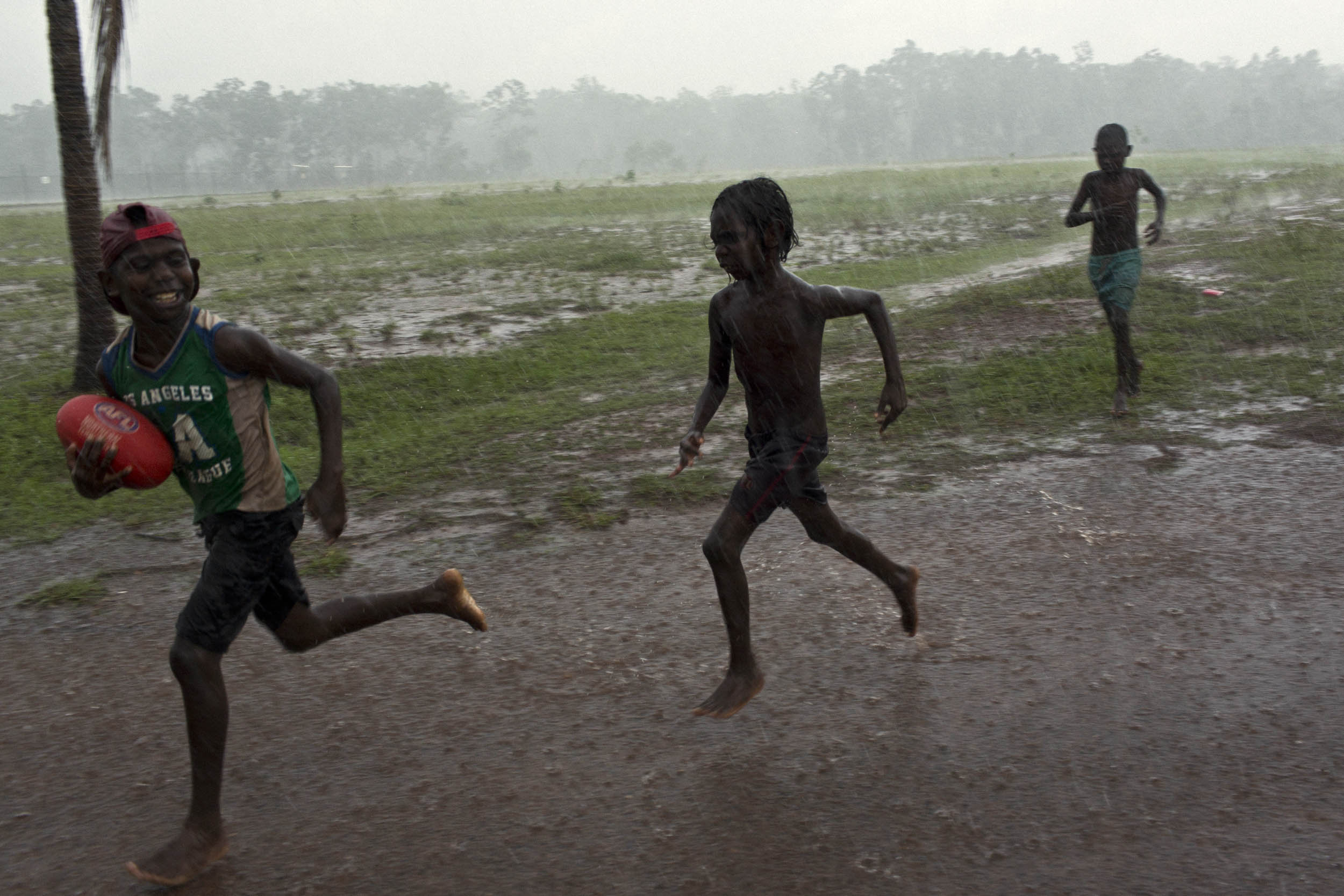 Boys play football in a rainstorm on Melville Island, Northern Territory.