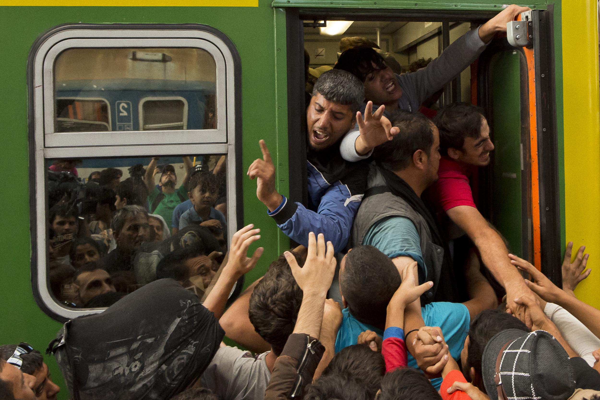 Budapest, Hungary. Refugees scramble to baord a bus in the central trainstation in Budapest.