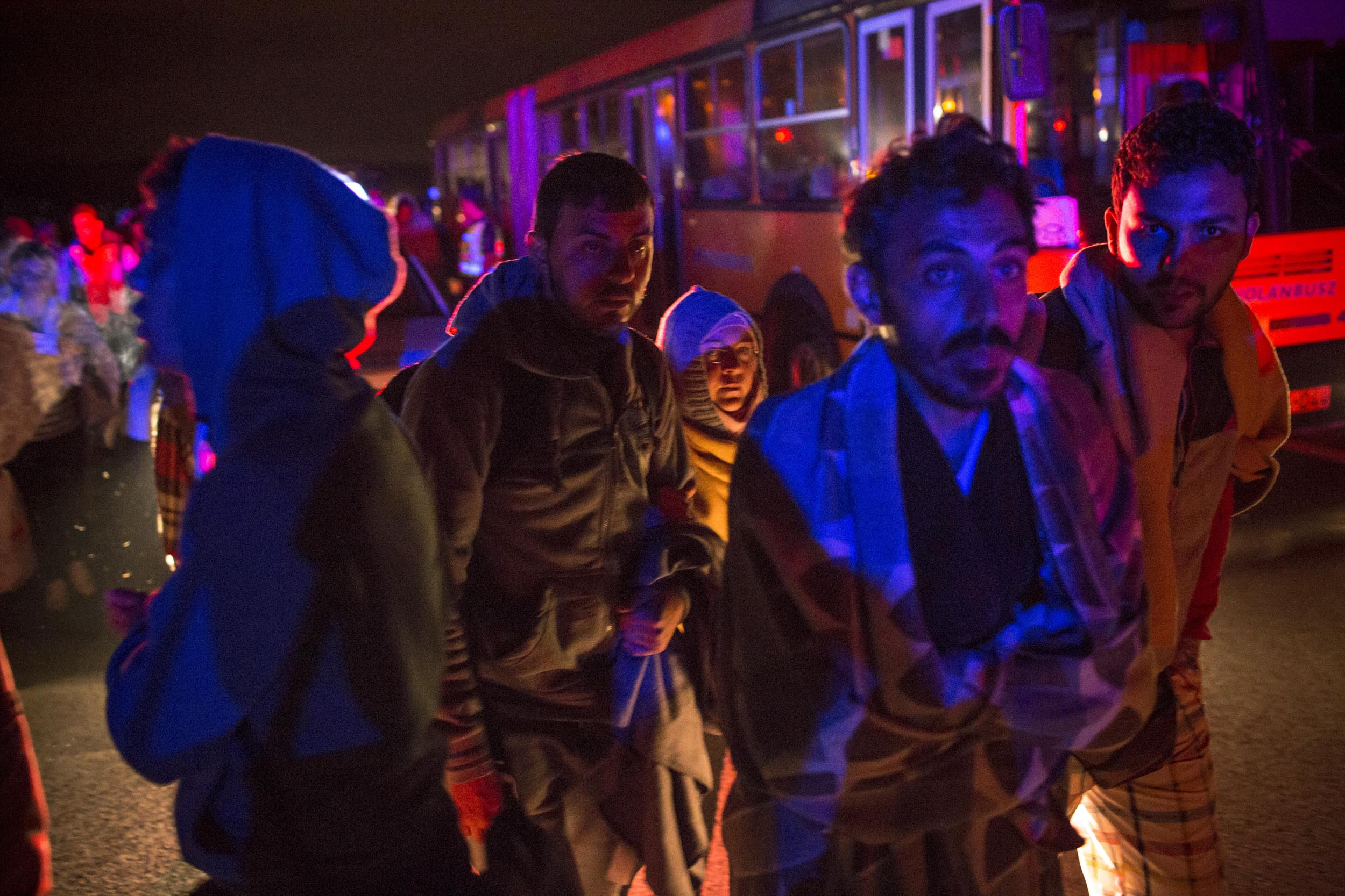 Outside Budapest, Hungary. Nervous refugees wait to board buses bound for the border between Hungary and Austria.