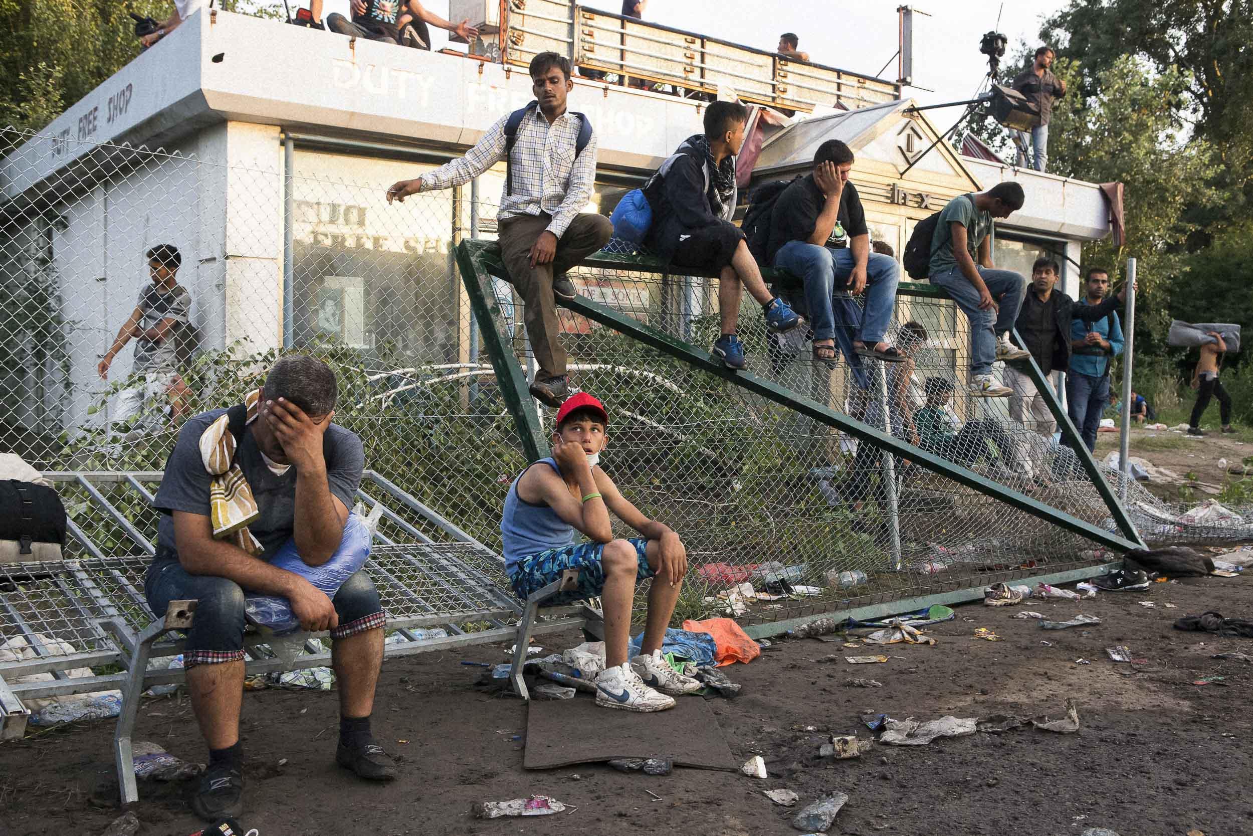 Horgoš, Serbia. Refugees rest on a damaged border fence after a violent clash with Hungarian police guarding the Serbian/Hungarian border.