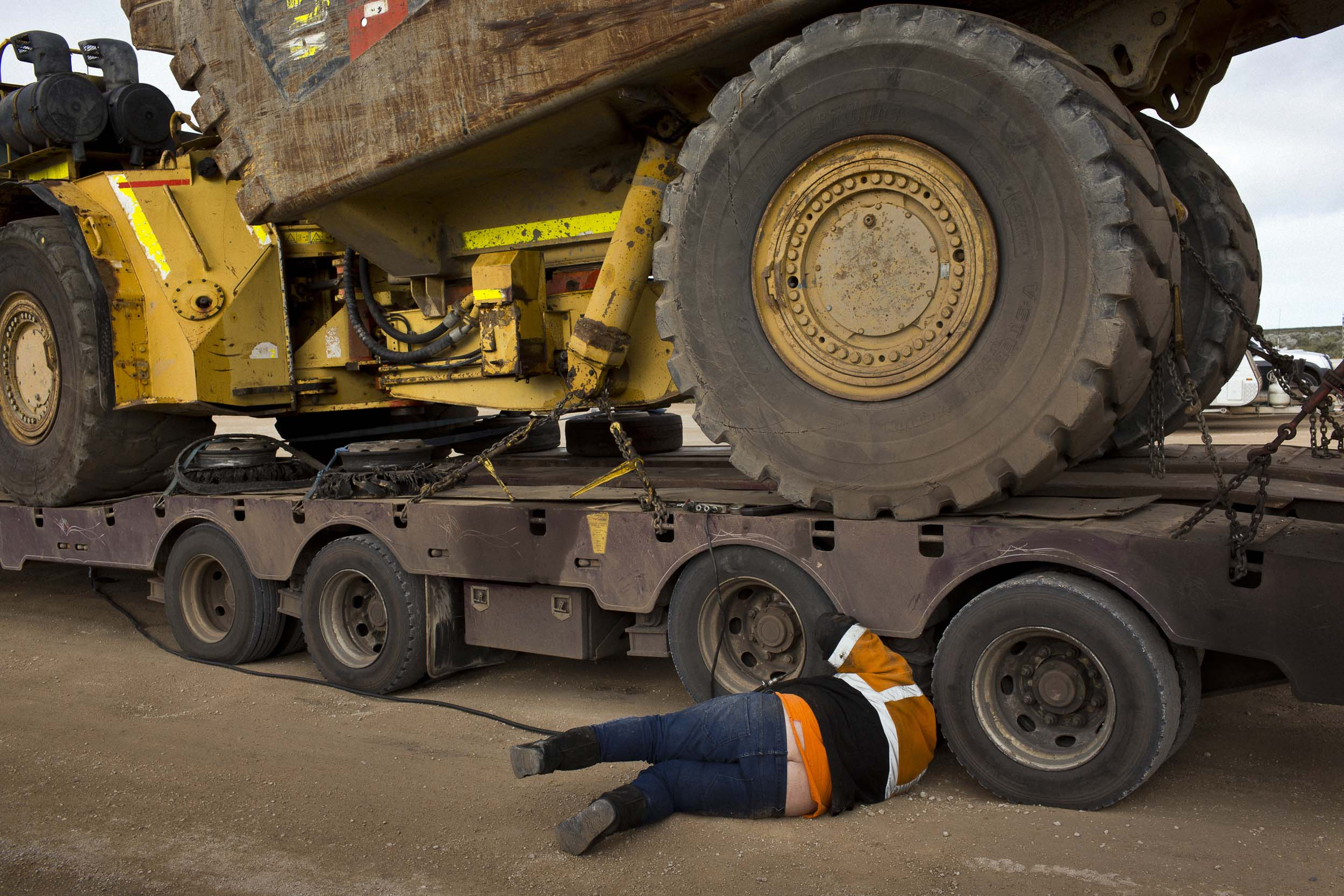 A truck driver inspects the tires on his trailer while stopped at the Nullarbor Roadhouse, Nullarbor, South Australia.