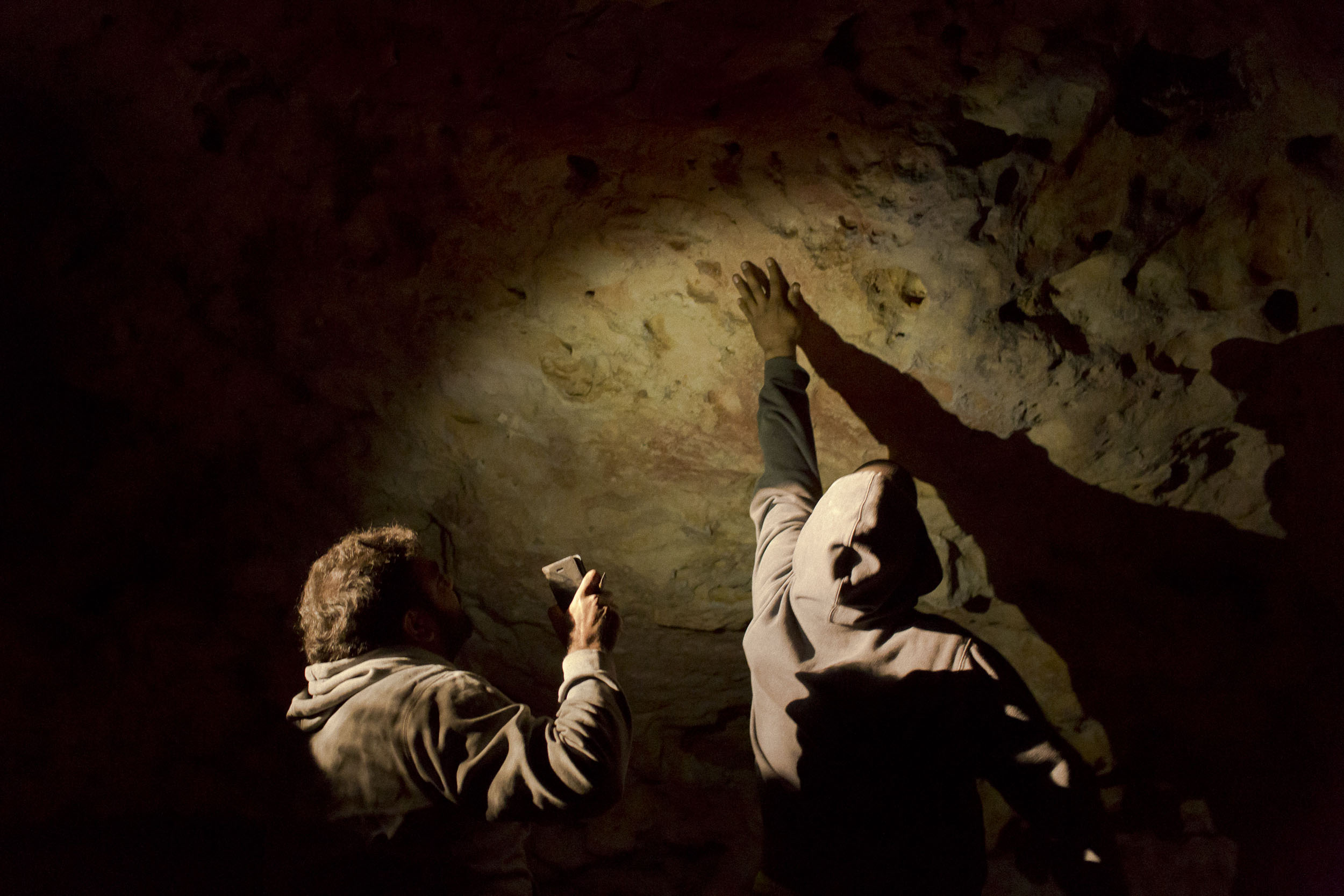 Pitjantjatjara Aboriginal men look at ancient paintings in a cave on the Nullarbor Plain, Yalata, South Australia.