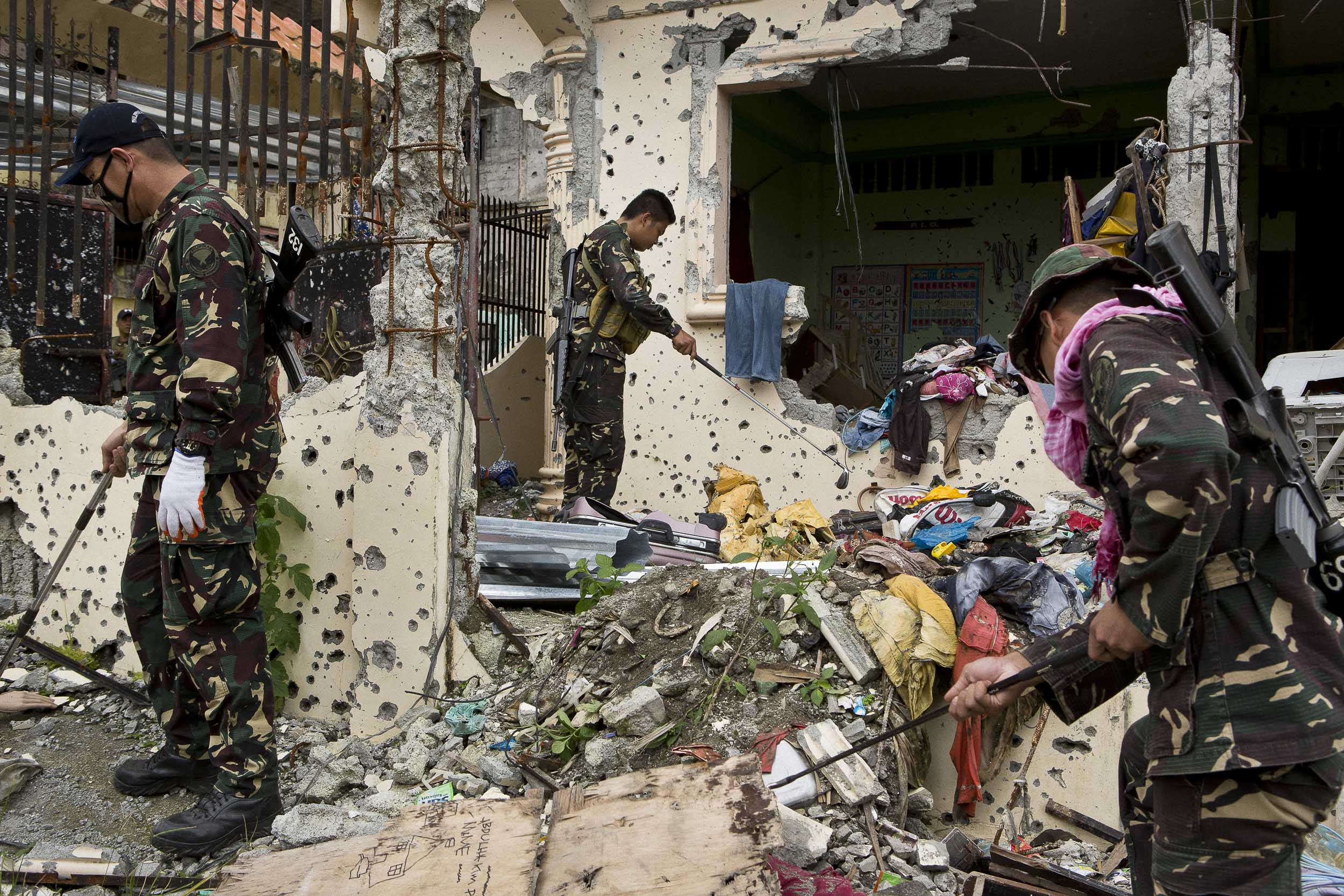 Members of a military joint task force working to clear the main battle area of Marawi of explosives comb through debris using golf clubs.