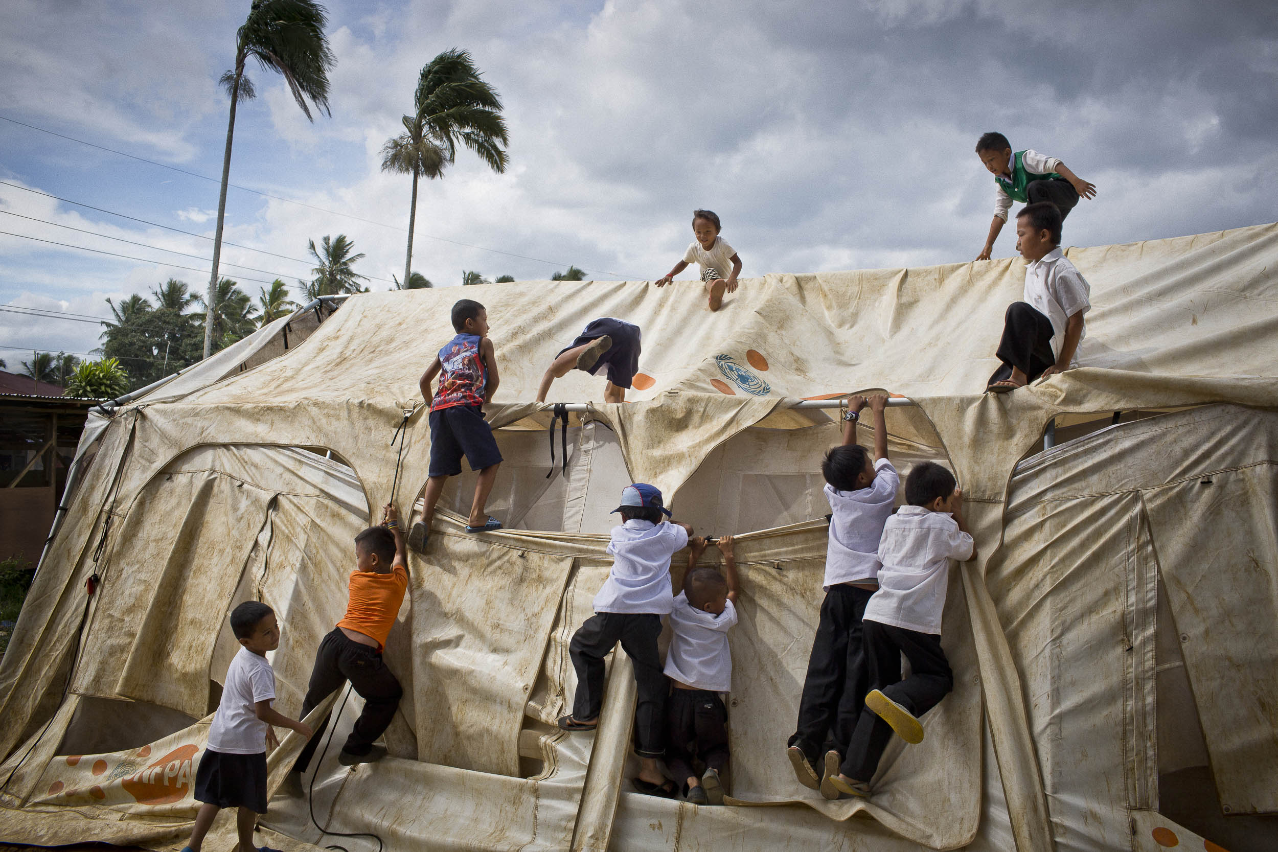 Children climb on a tent set up by a relief organization to accommodate children displaced by the fighting in Marawi at the Saguiaran Central Elementary School. The school saw its population double to accommodate children living in an IDP camp nearby.