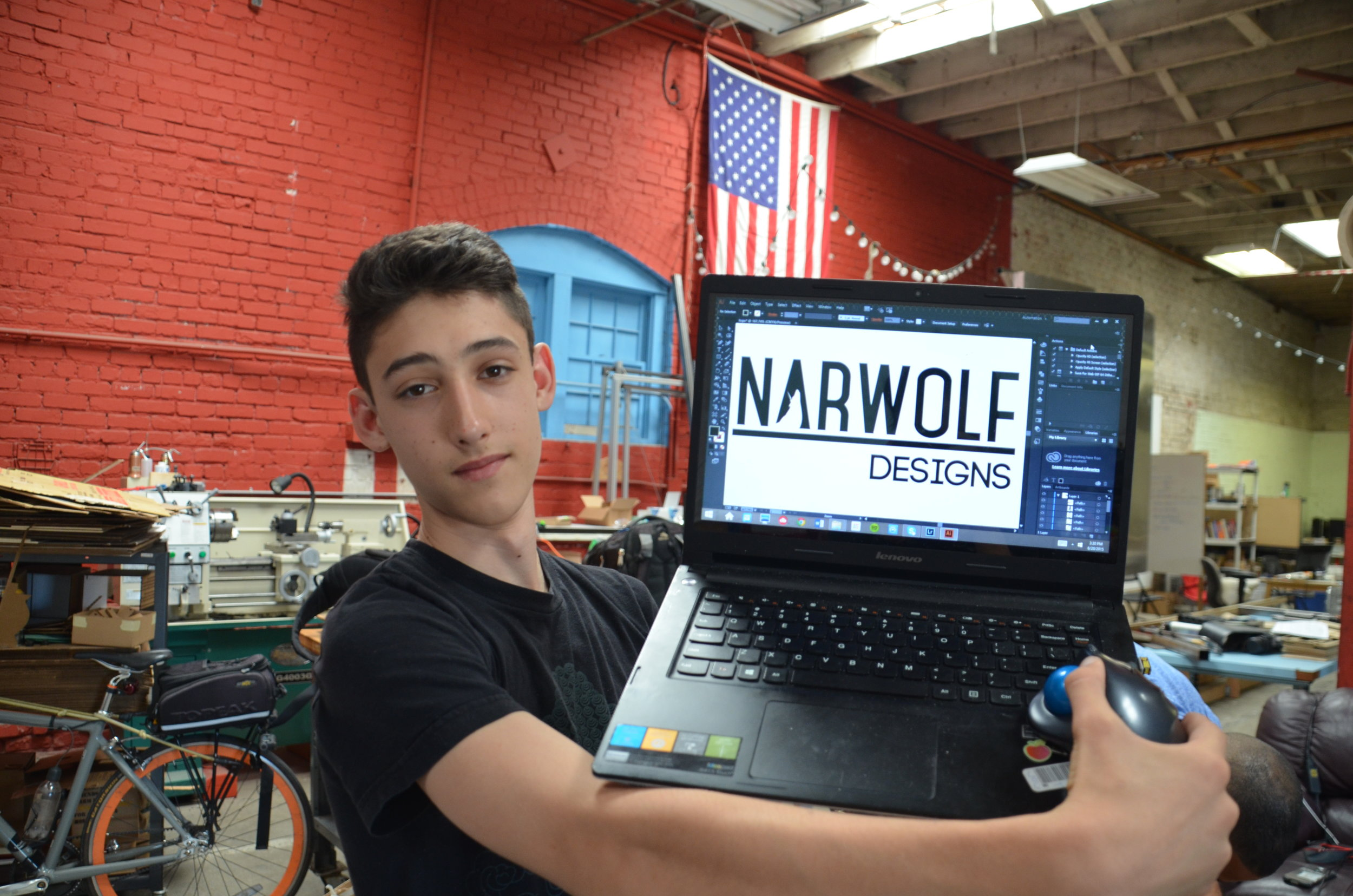 Students showing narwolf design logo on laptop