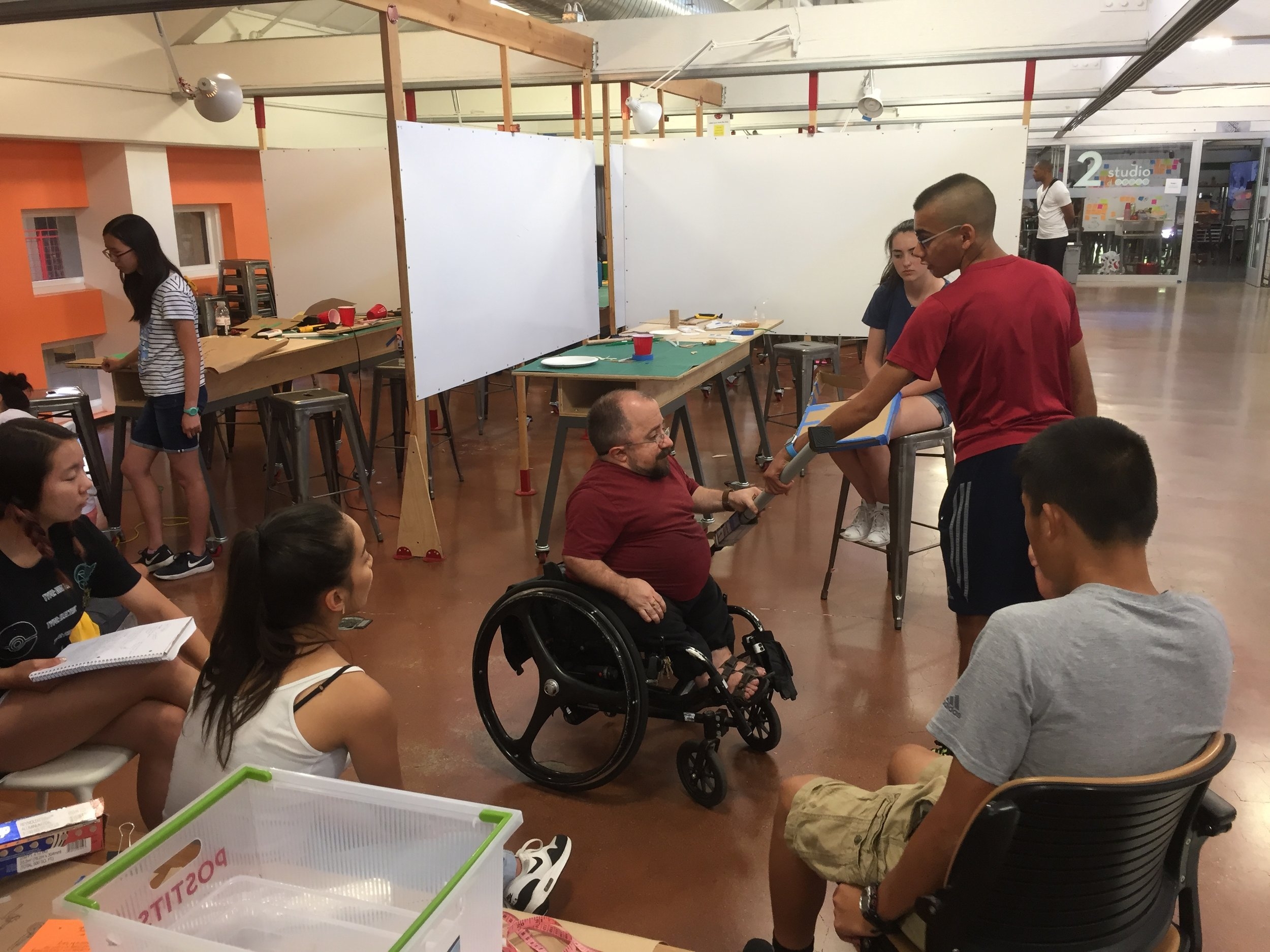 Man in wheelchair greets students