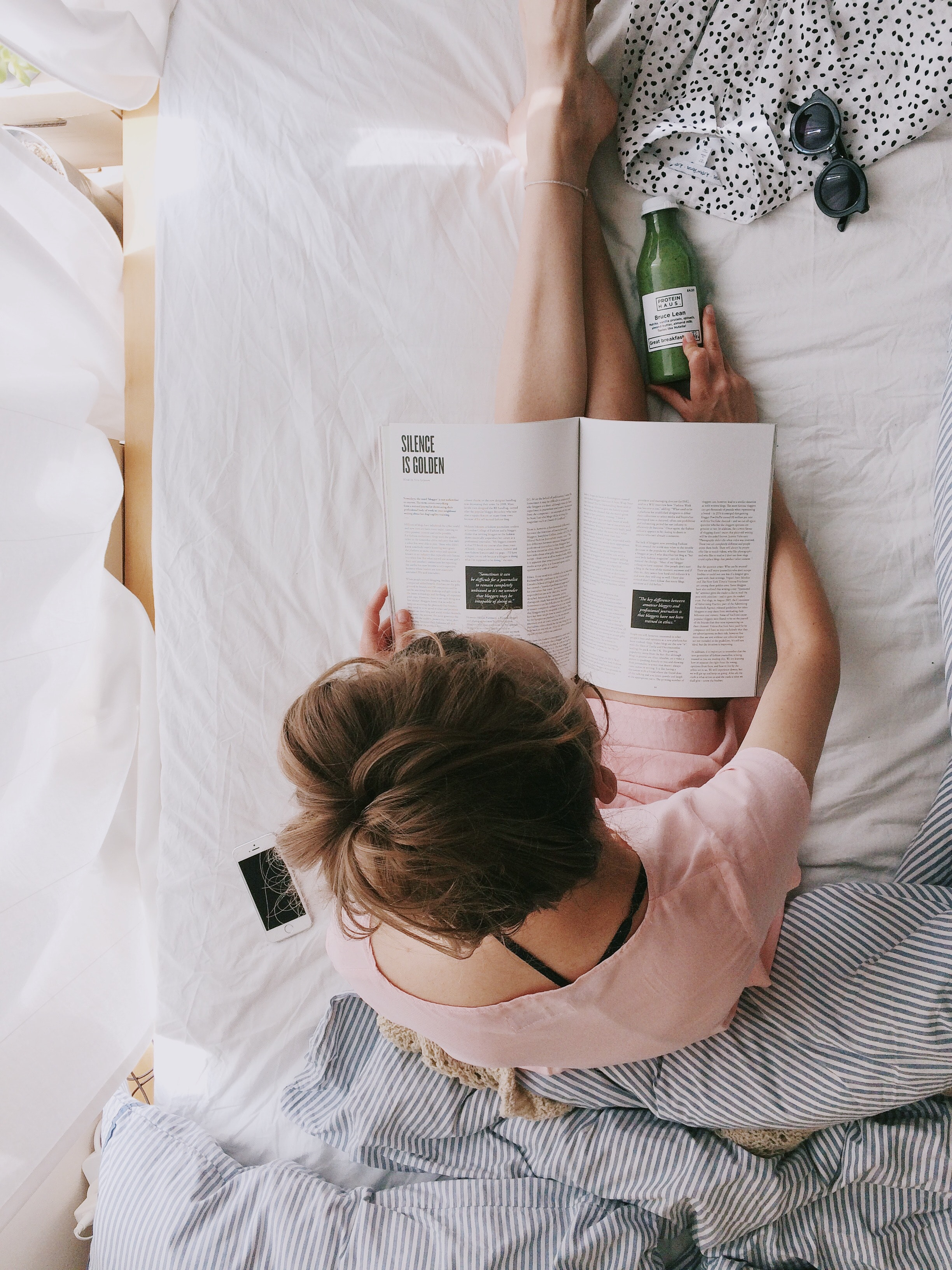 Image of influencer (woman) reading magazine [Source: Unsplash].