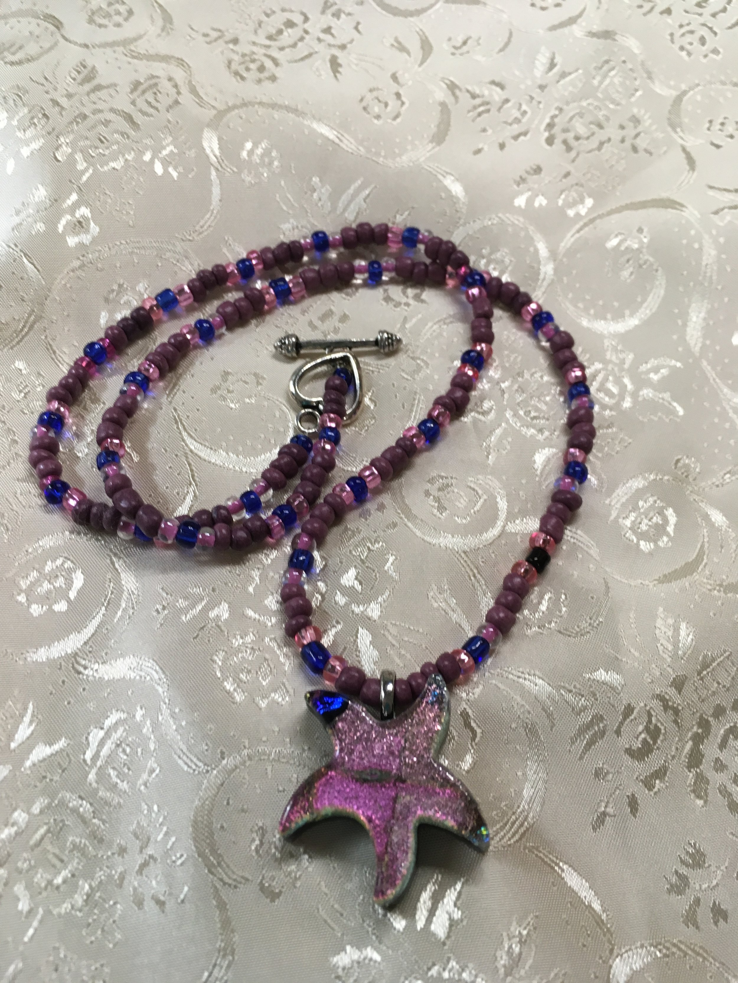 "From the sea, a stunning dichotic Starfish in shades of pink and purple with a touch of royal blue that glisten in the light. The hand beaded necklace is 21 "" long . $32.00"