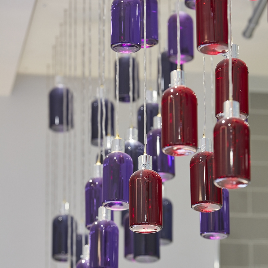 Hanging Red and Purple Molton Brown Bottles with wire coming from lid with LED light