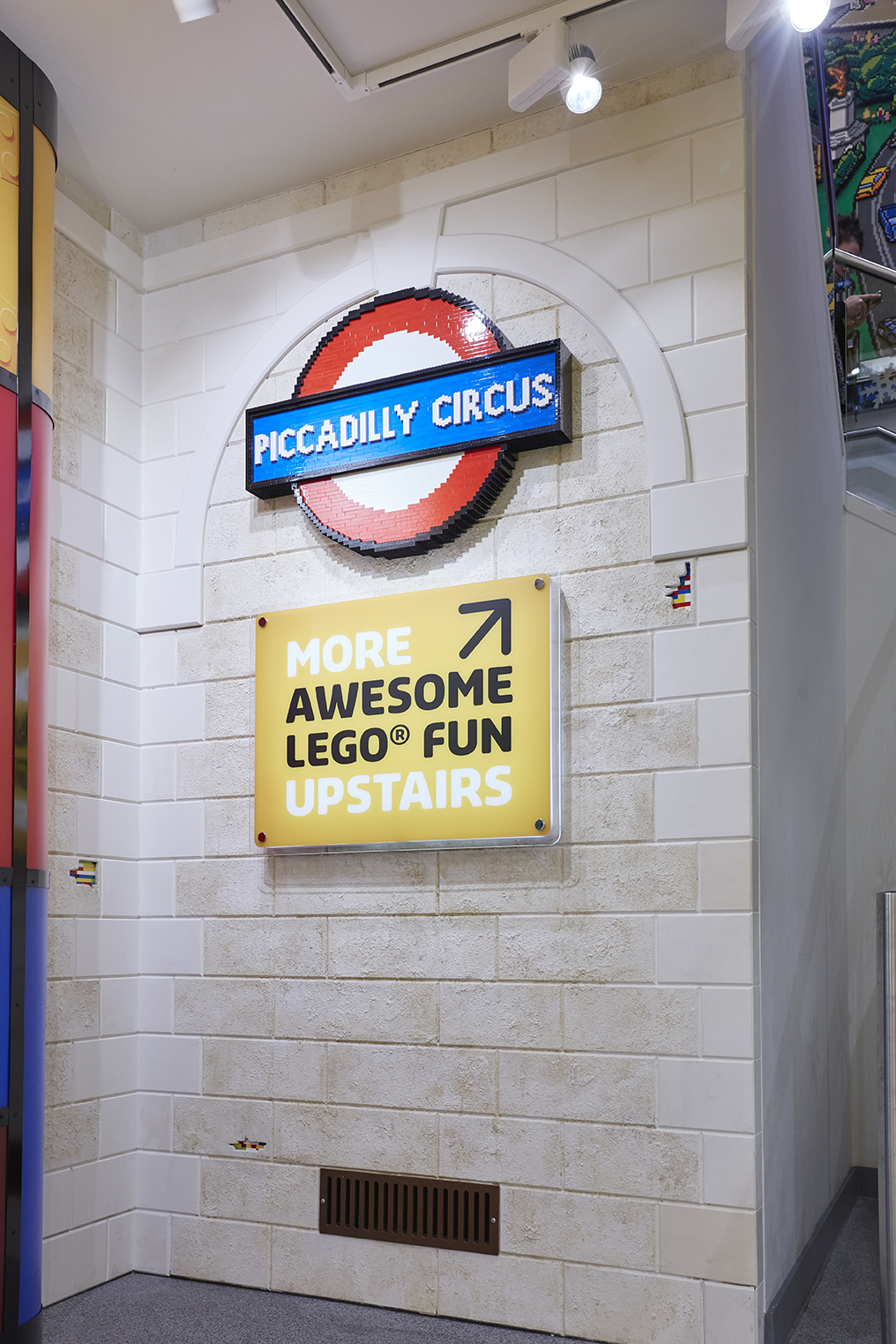Piccadilly Circus tube station LEGO sign with illuminated directional signage below
