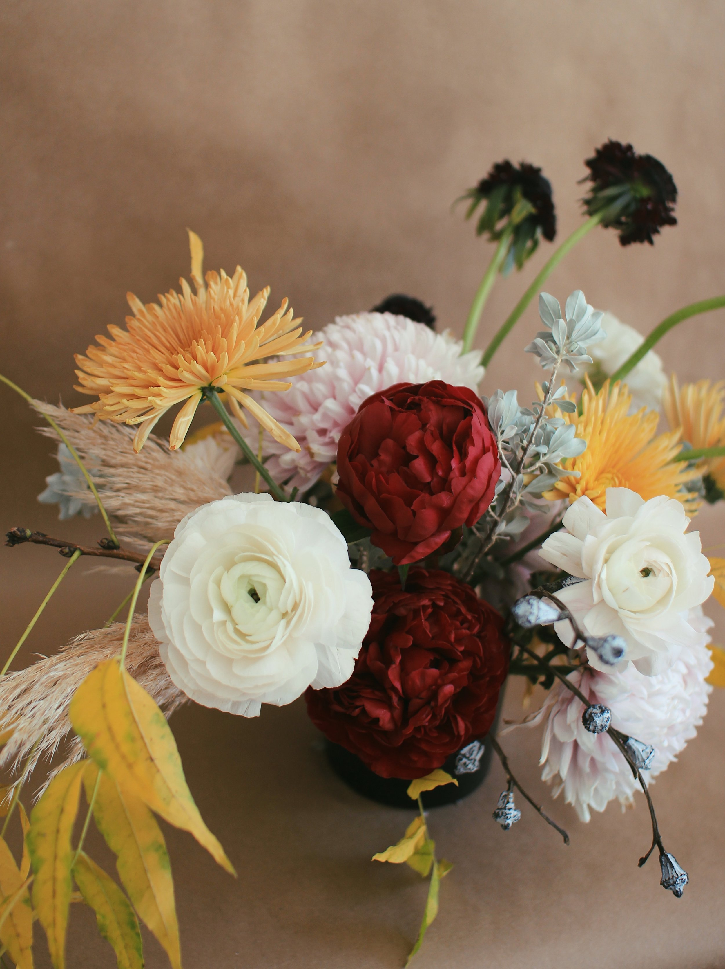 CLOONEY RANUNCULUS, RED CHARM PEONIES, ORANGE SPIDER MUMS, SILVER BELL PODS, PAMPAS GRASS, FALL FOLIAGE
