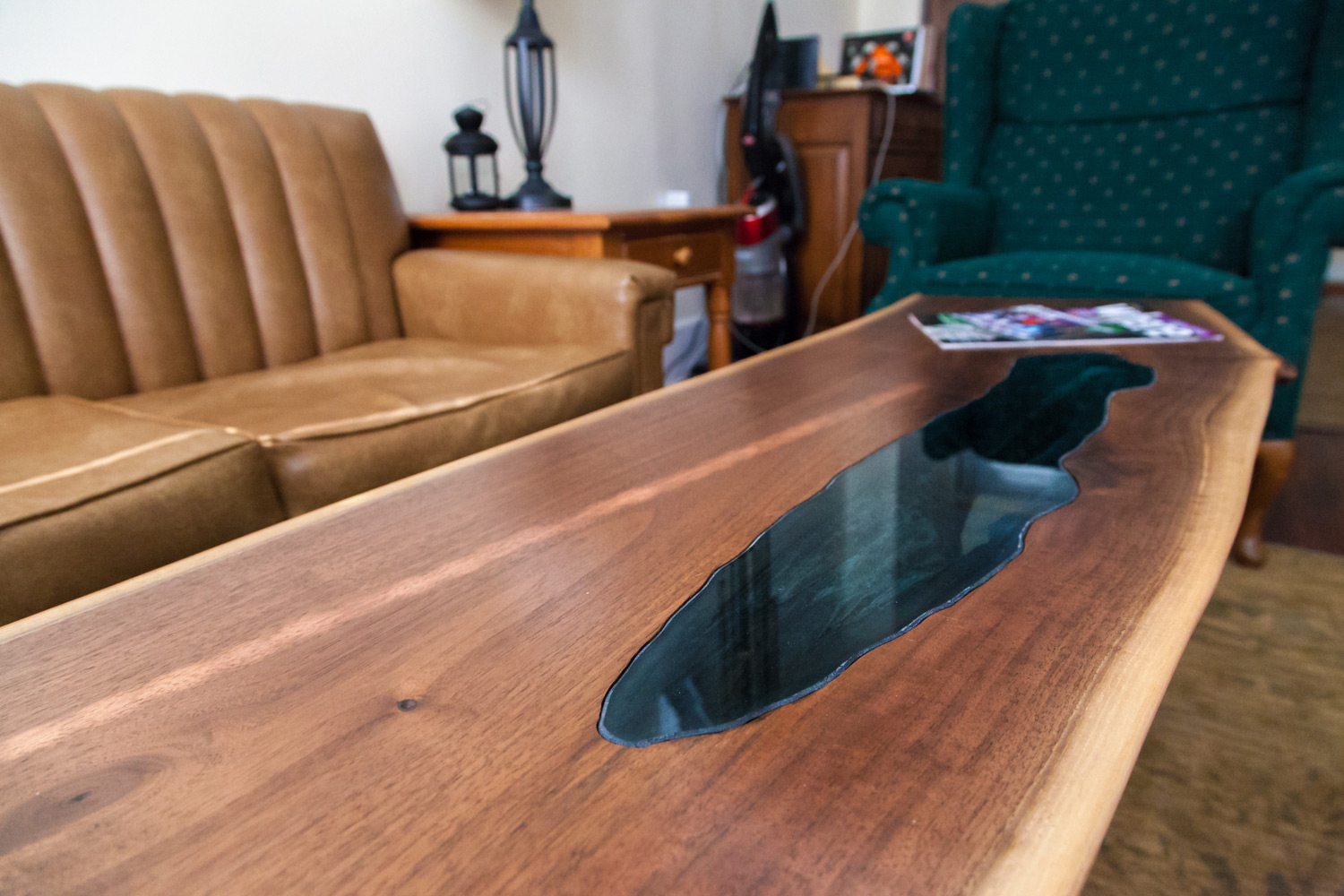 Logs do not have defects, only character. We celebrate the missing section in this walnut table with a section of inlayed blue glass. The result gives the impression of a serene mountain lake.
