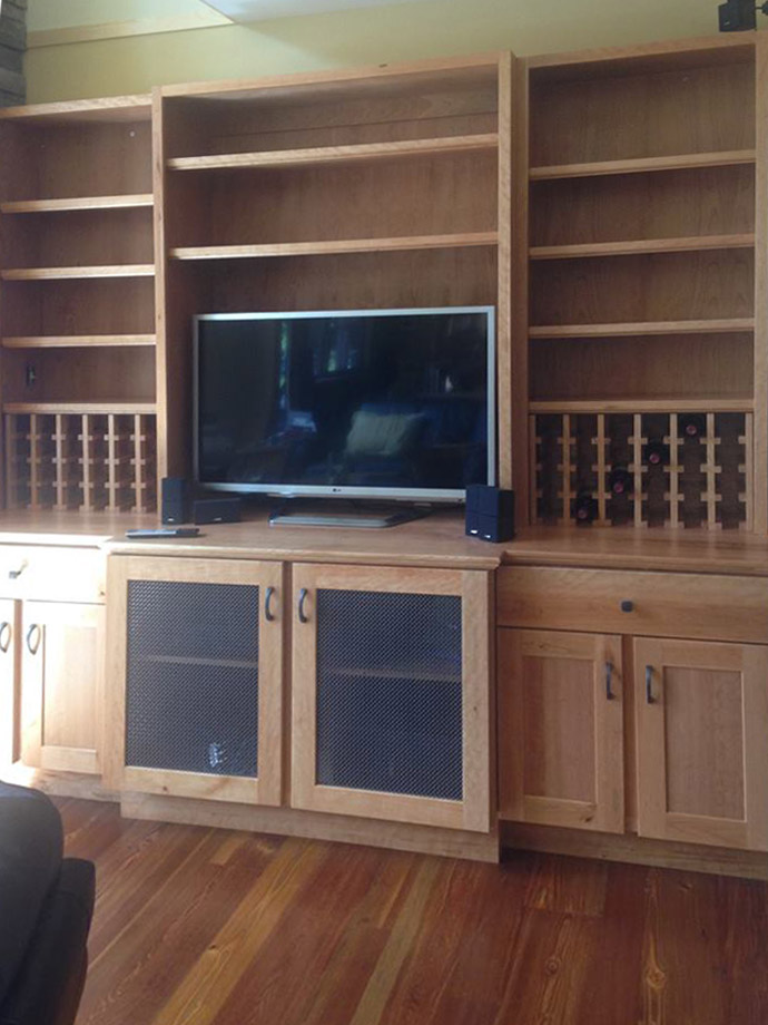 This large cherry entertainment center hides the surround sound equipment while allowing the deep subwoofer tones to travel unimpeeded by the mesh doors.