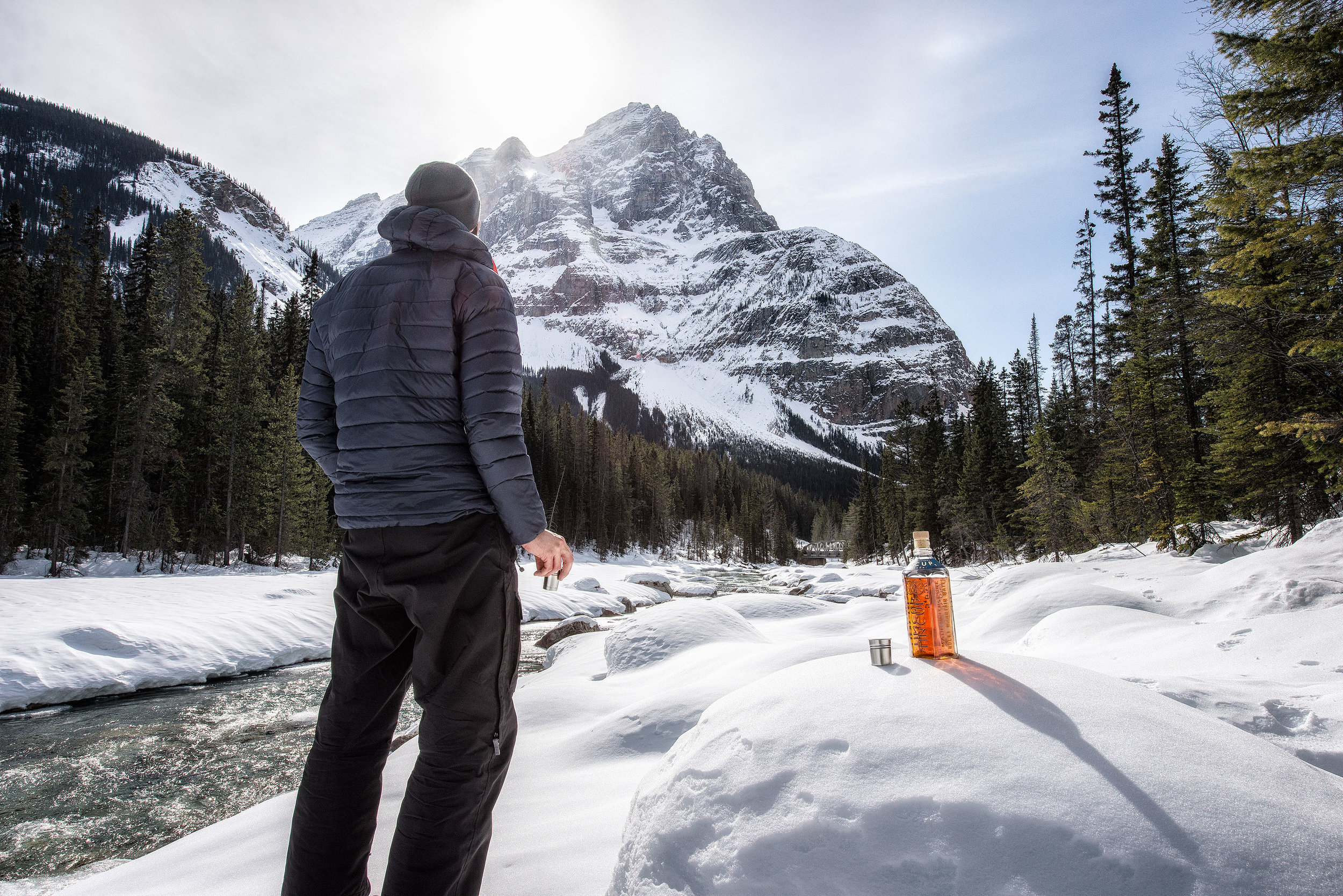 austin-trigg-whiskey-banff-alberta-product-TINCUP-Field-Alberta-River-bottle-snow-day-time.jpg