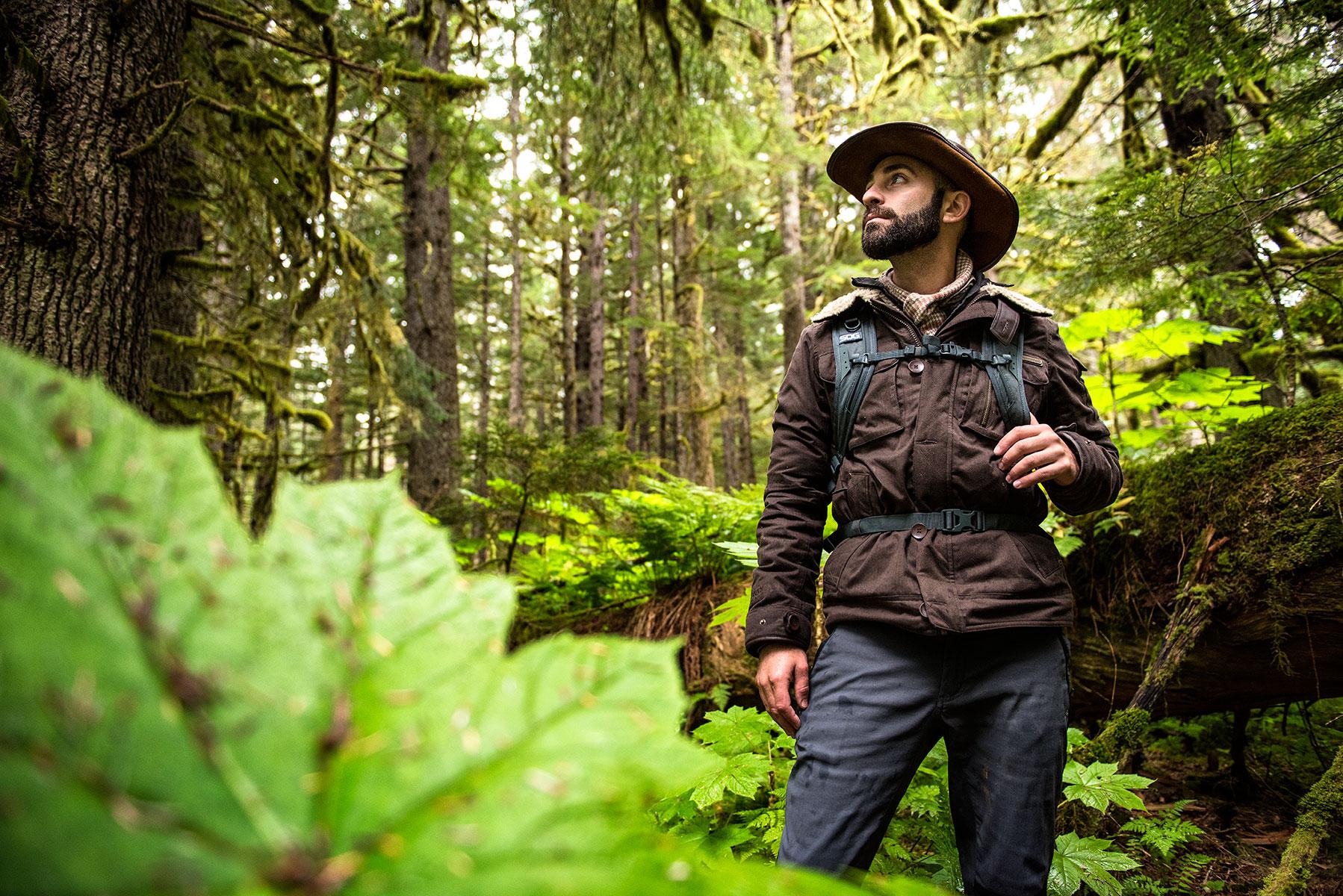 austin-trigg-brave-wilderness-alaska-BW-Coyote-Stands-Next-to-Bush.jpg