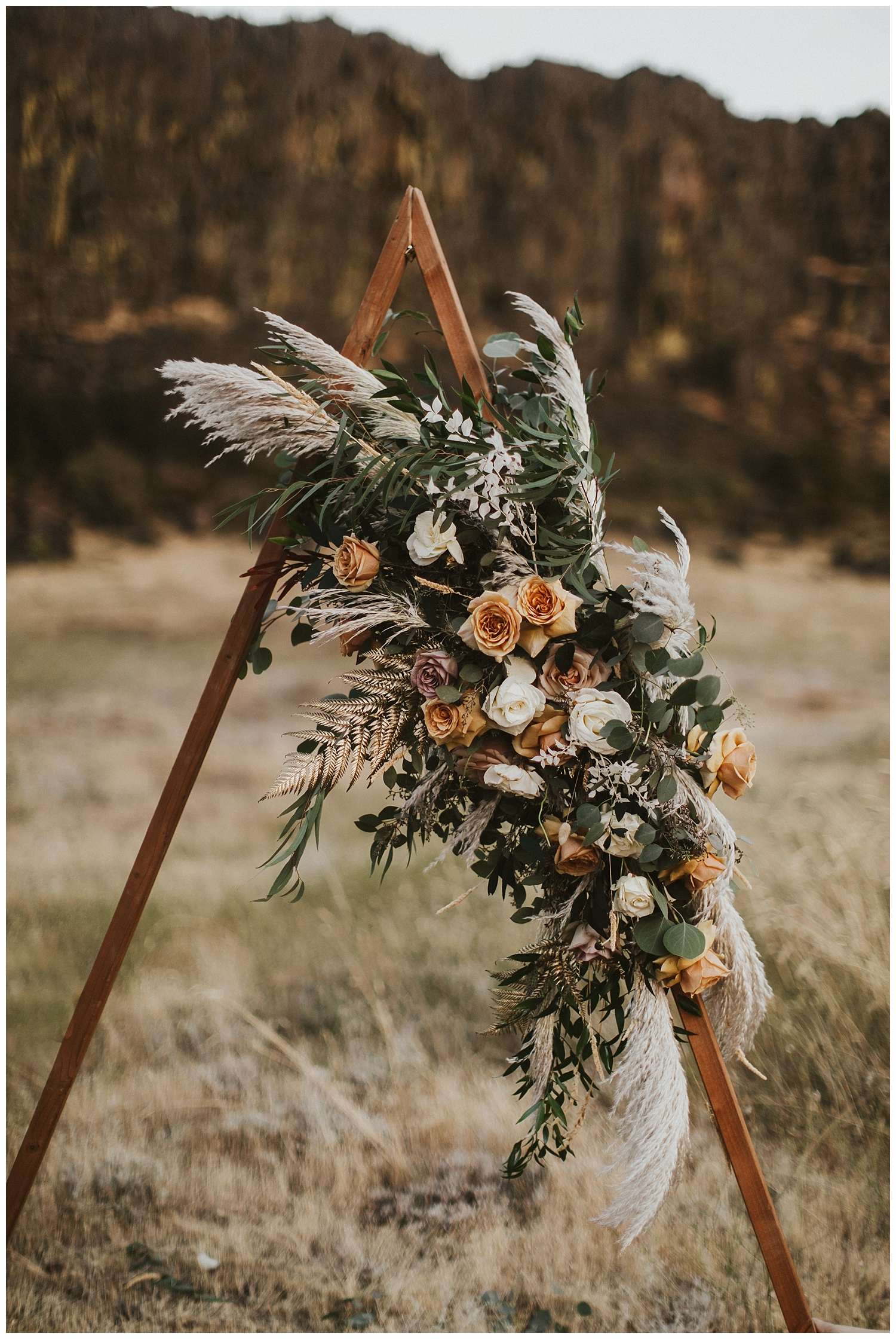 a wooden triangle arch with dried leaves and beautiful boho flowers