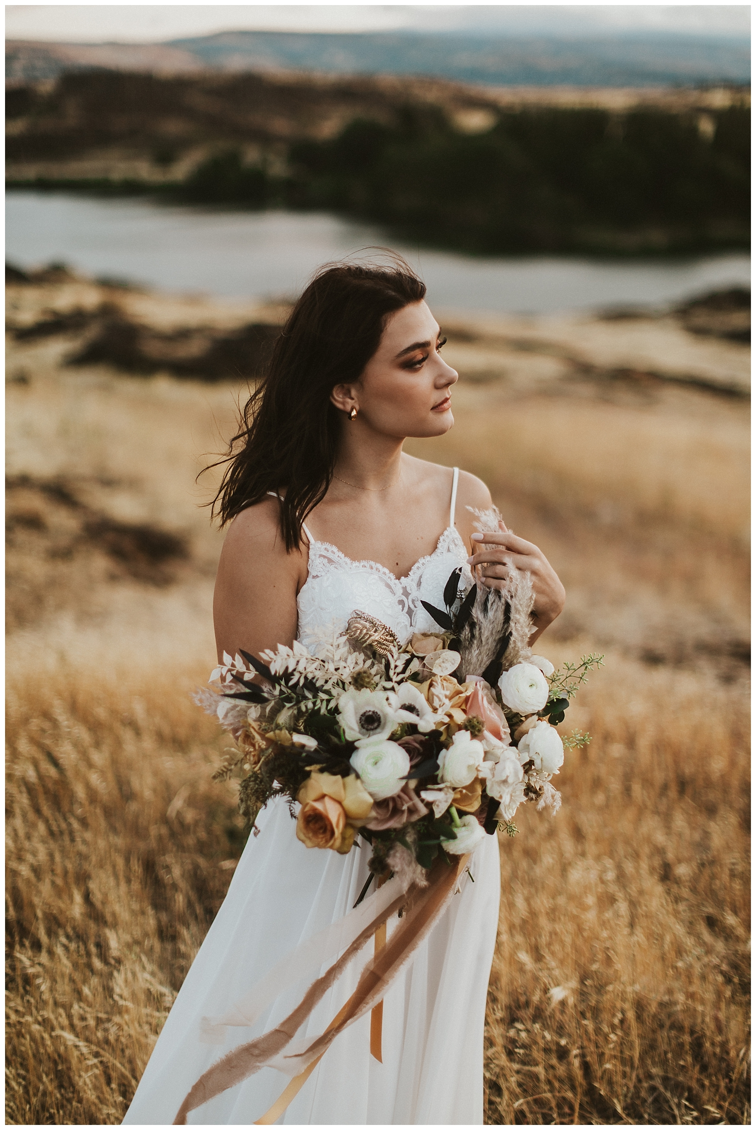 a bride in a flowing white gown holds a large bouquet and looks off into the distance
