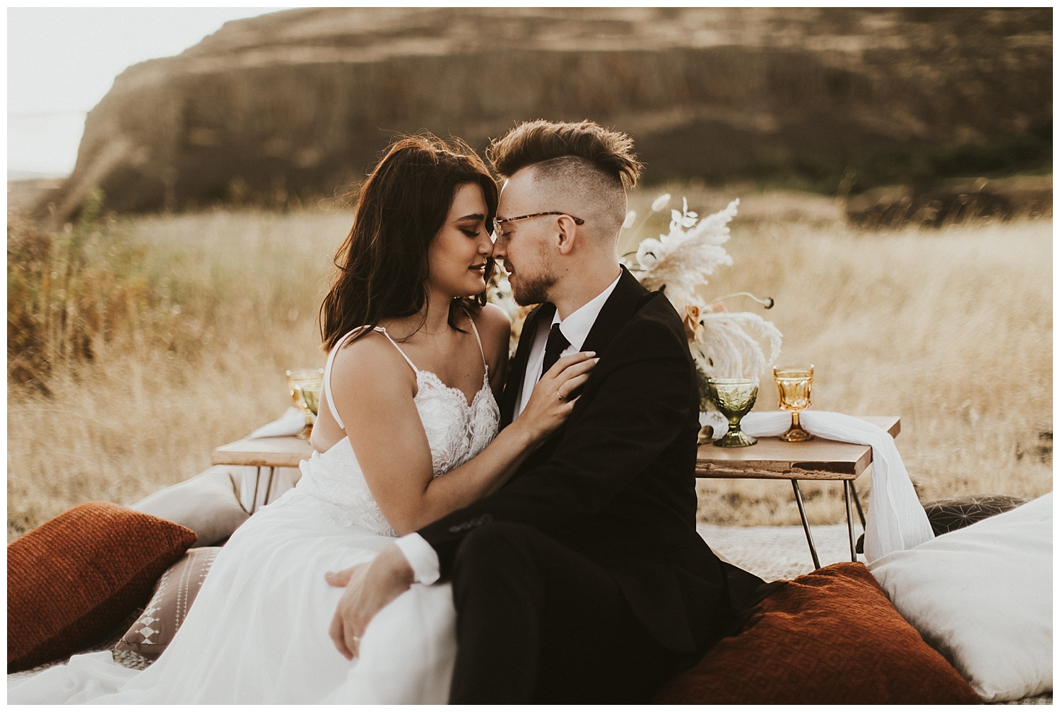 a bride and groom sit at their boho picnic in the desert and snuggle up to one another