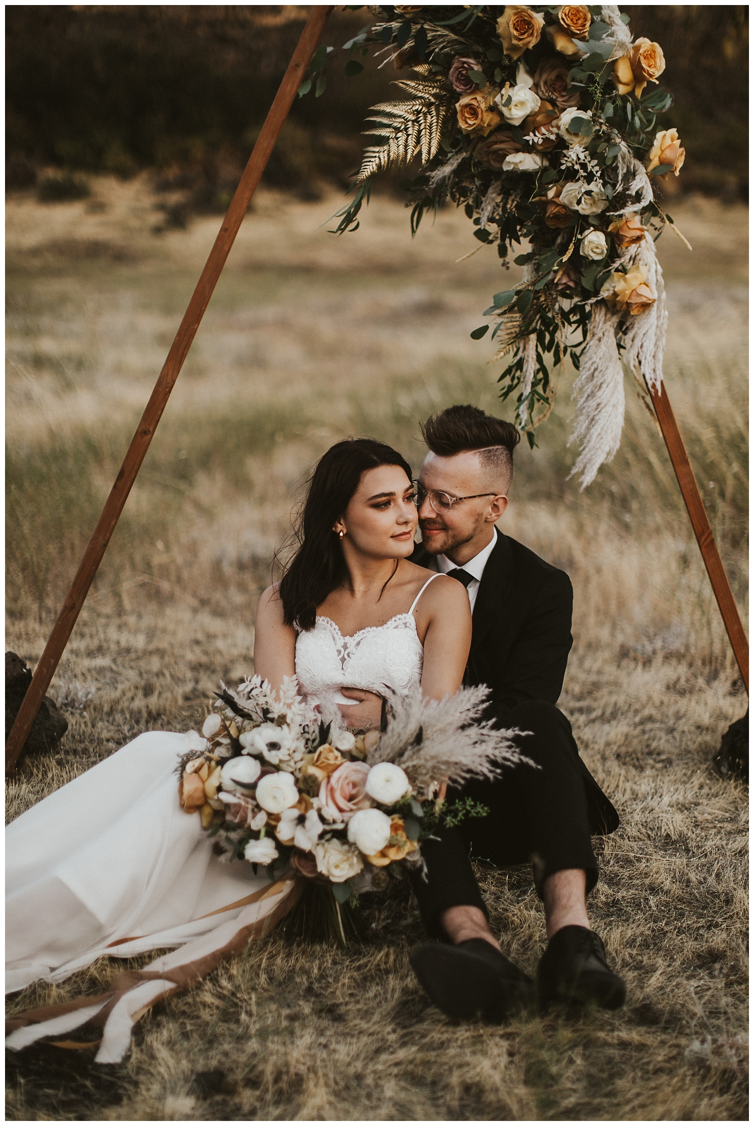 a boho bride and groom sit together under their wooden triangle arch in the desert