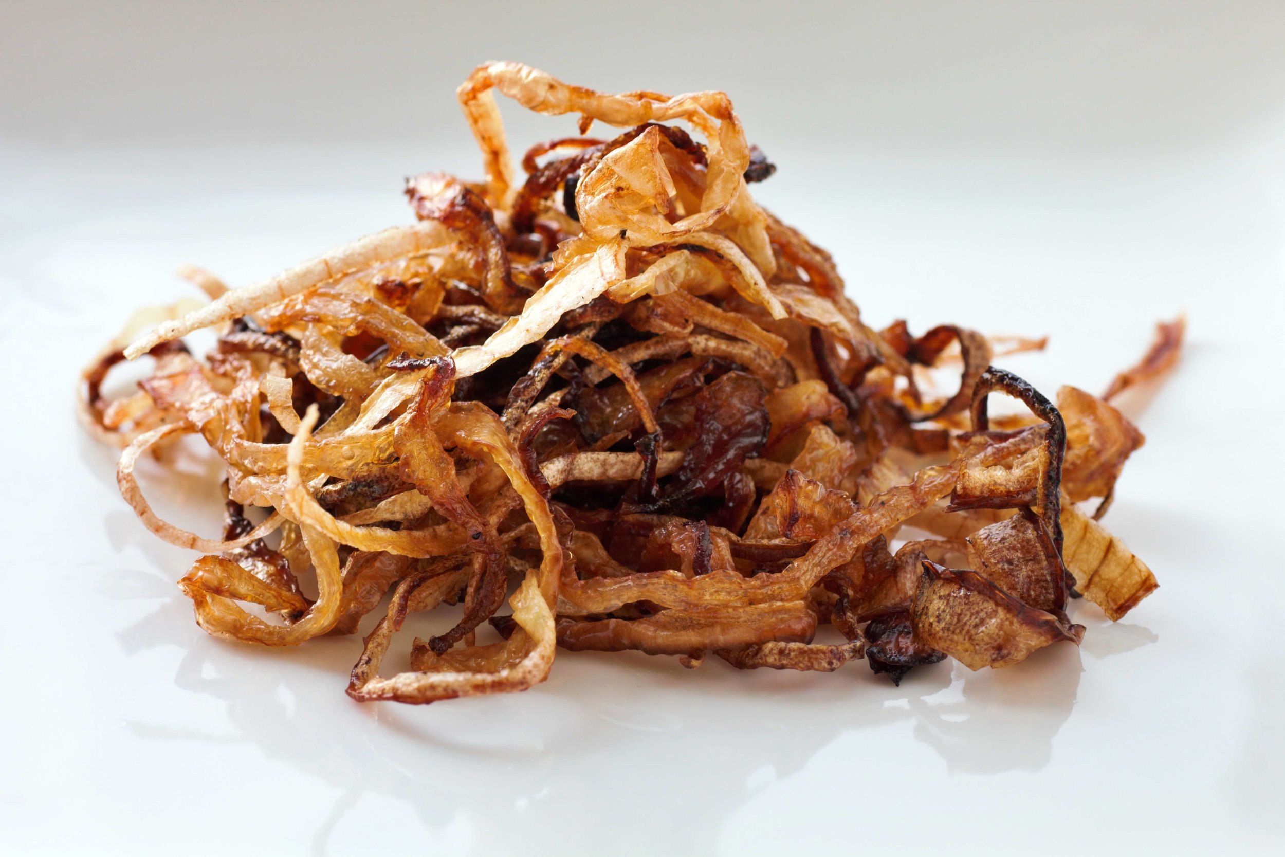 Keto fried onions make perfectly crispy strands of onion, delicious on everything from steaks to sandwiches. Best of all, there's no breading needed!