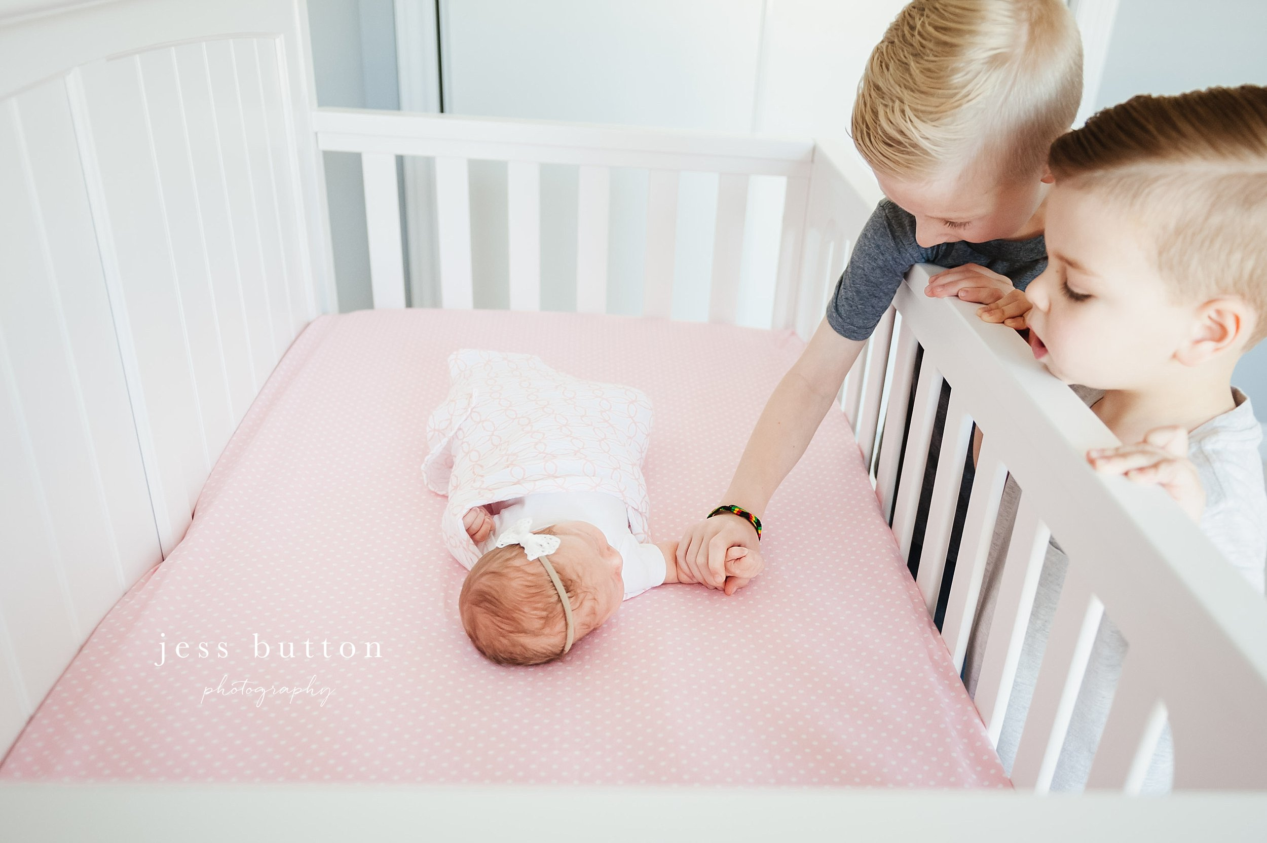siblings in baby room reaching into crib