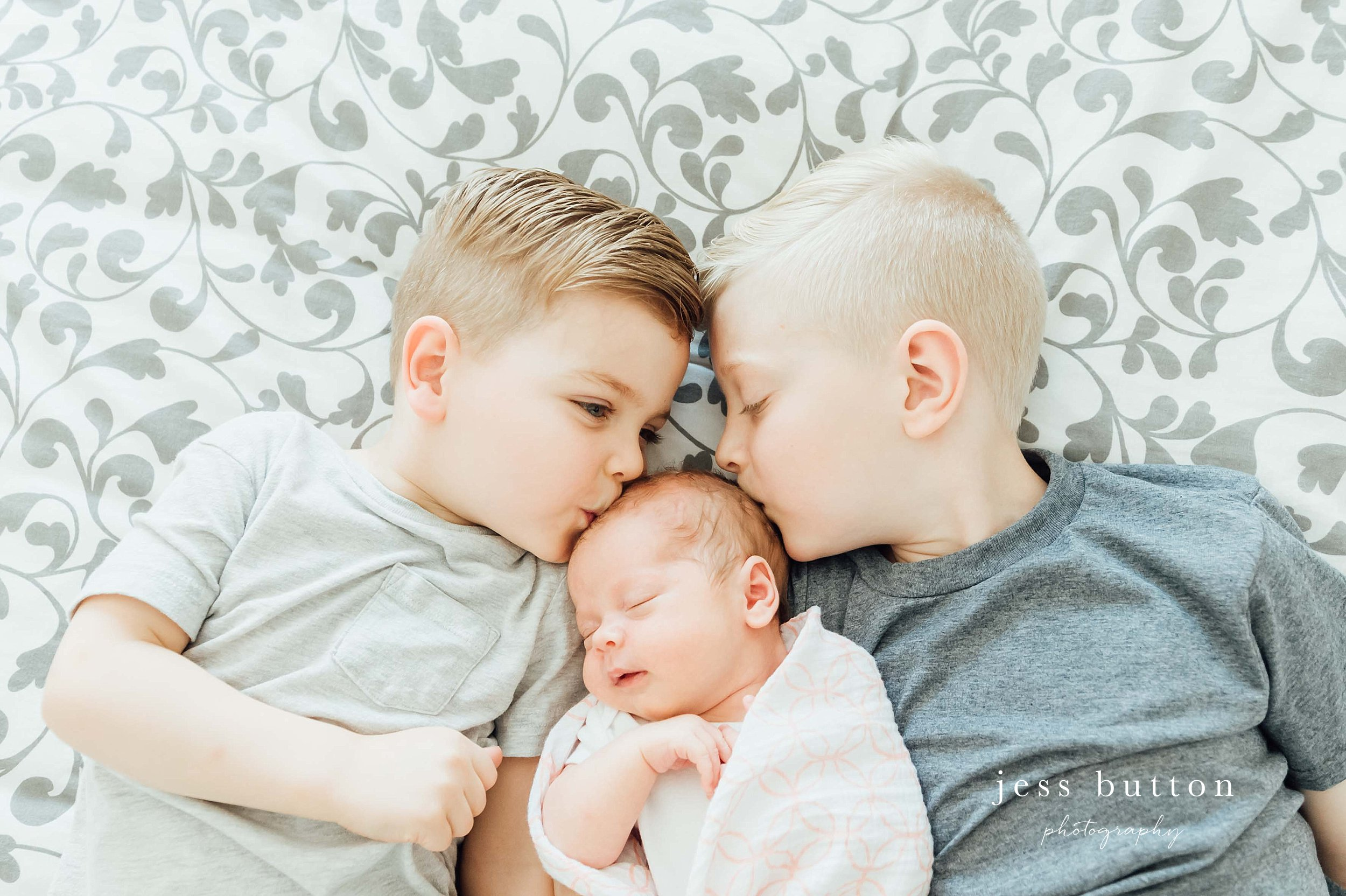 brothers and sister laying together with newborn baby girl