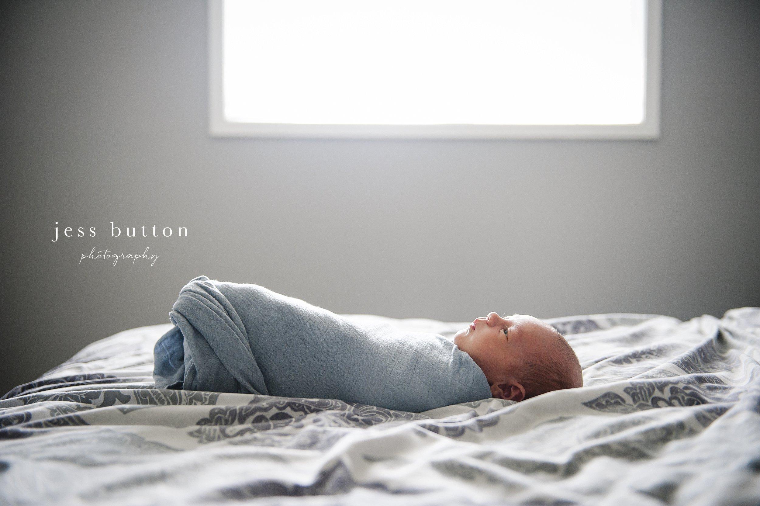 swaddled baby laying on bed awake
