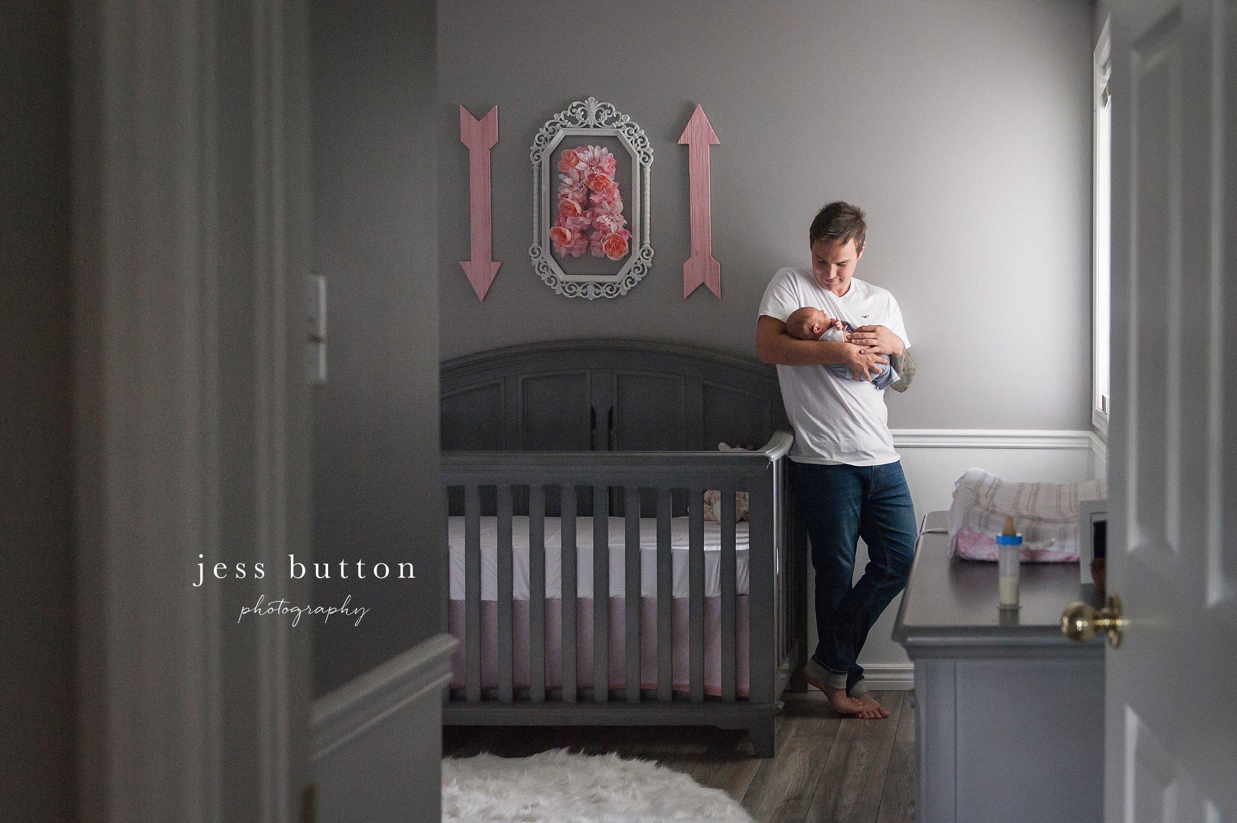 new dad holding newborn girl in nursery by window