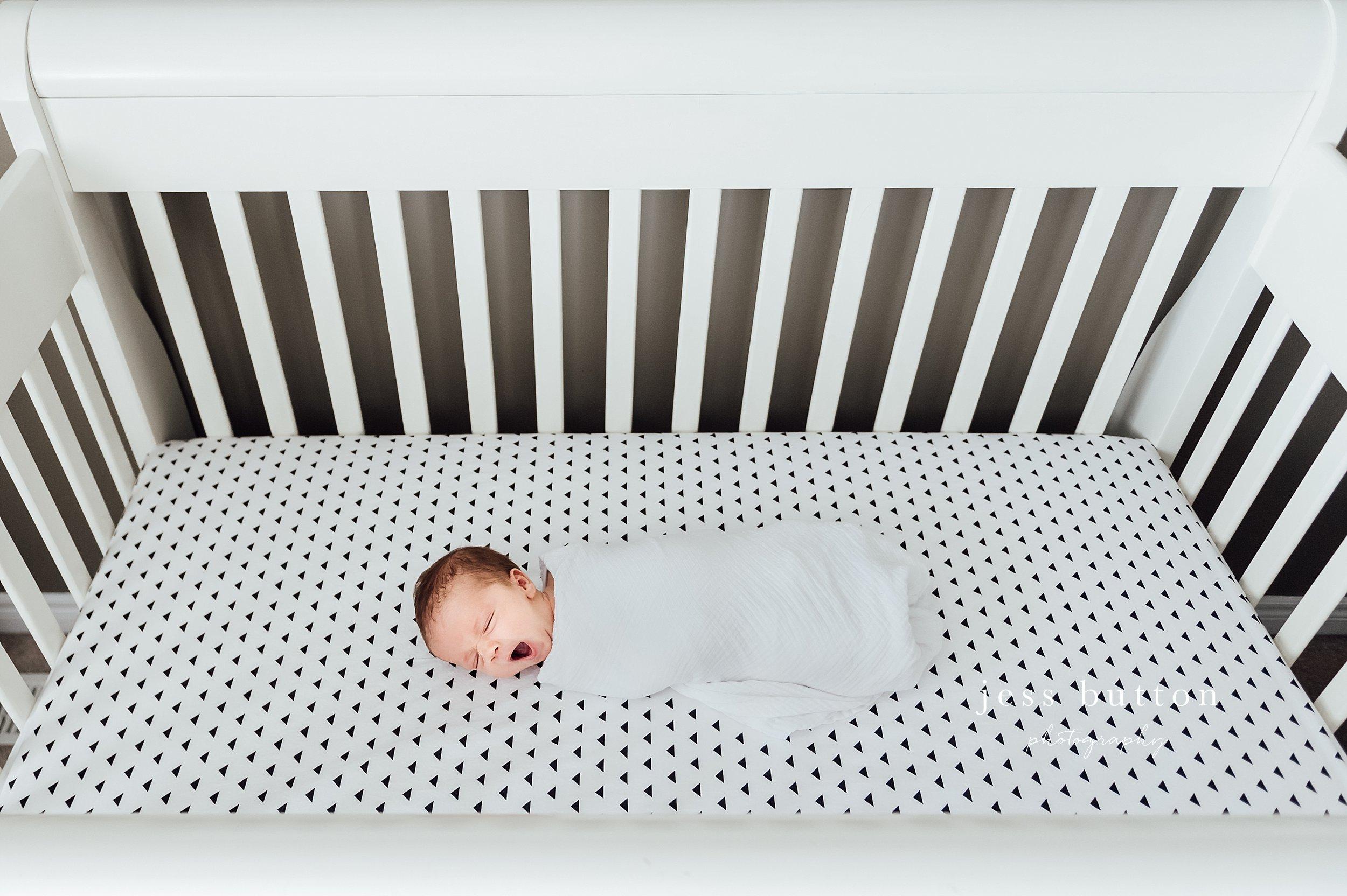 baby swaddled in crib yawning