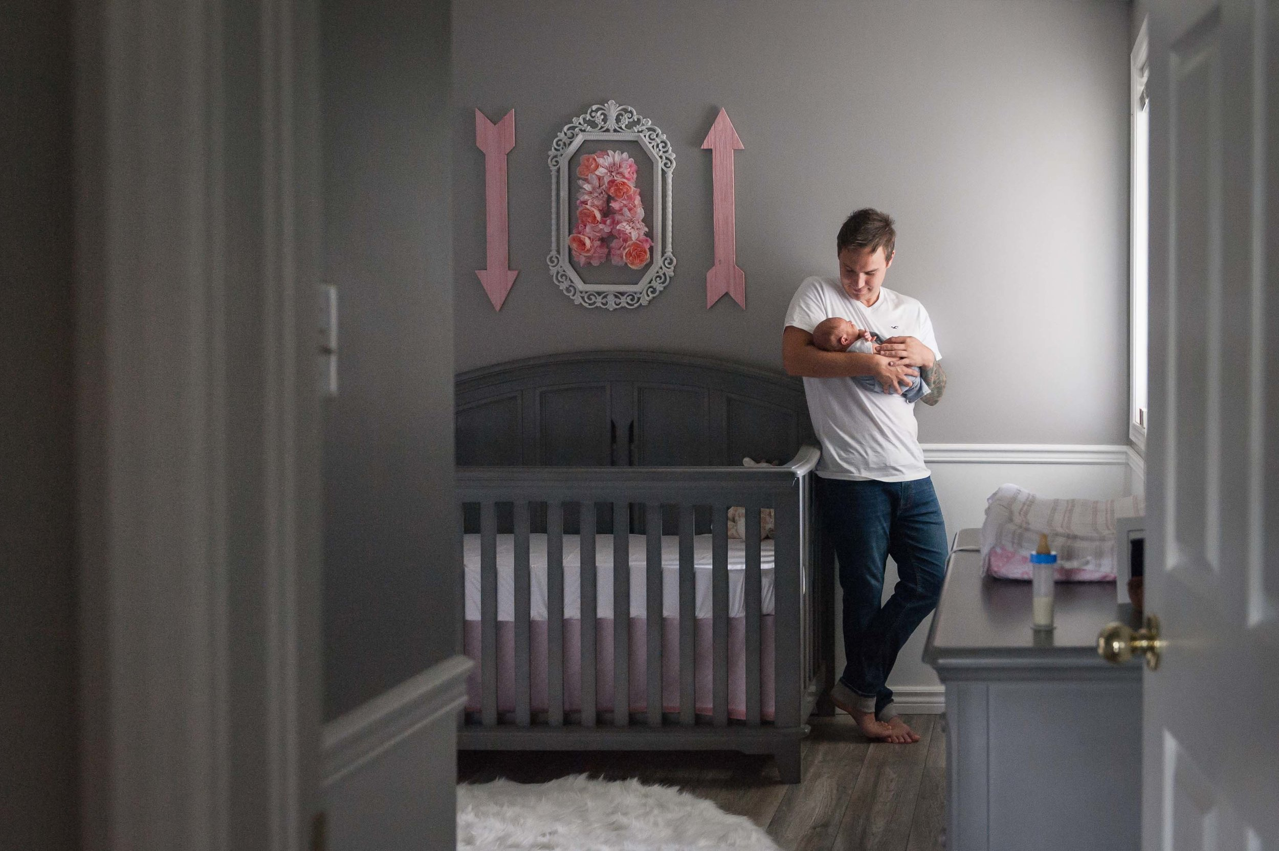 dad holding baby girl in grey and pink nursery - niagara lifestyle baby photographer