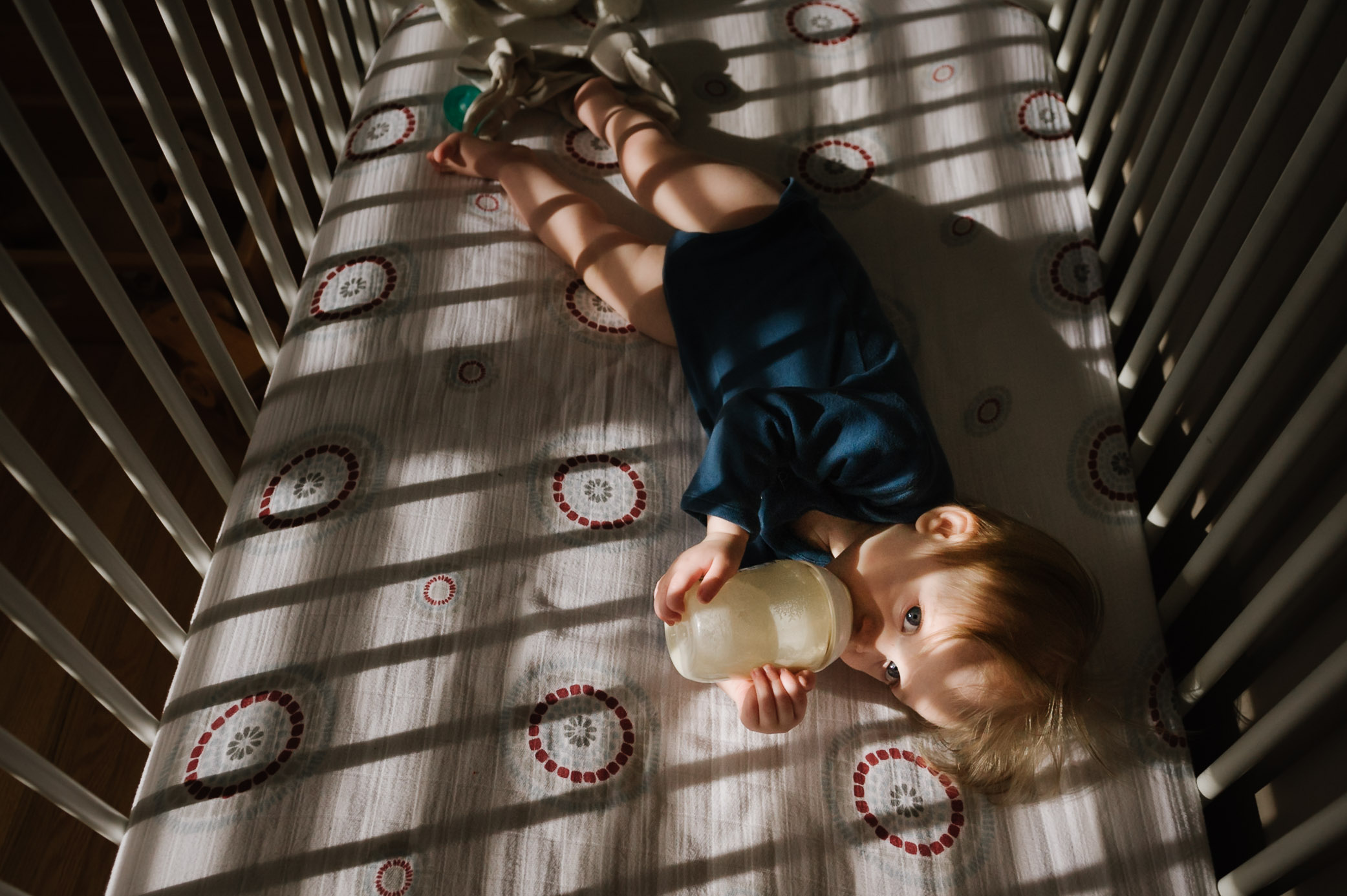 boy drinking bottle in bed - St Catharines baby photographer