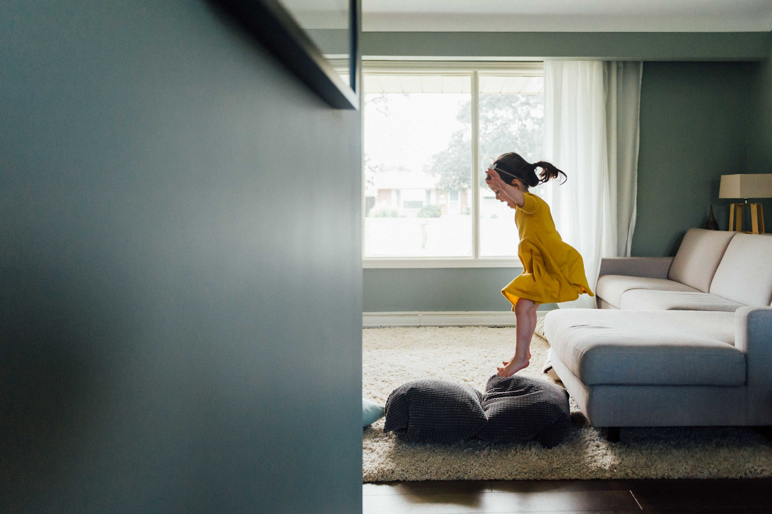 girl in yellow dress jumping on couch - Niagara in-home family photography