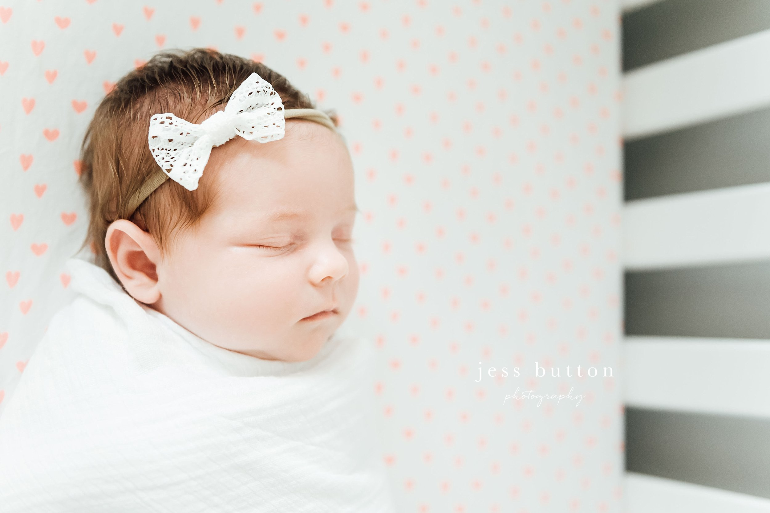 baby girl with lace bow in crib pink sheets - Fonthill - Niagara Newborn Photography